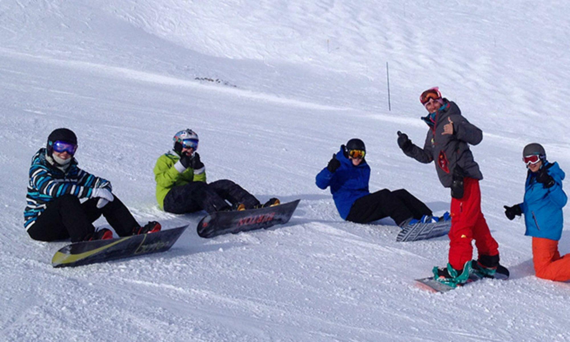 Un groupe de snowboardeurs lors d'un cours collectif de snowboard.