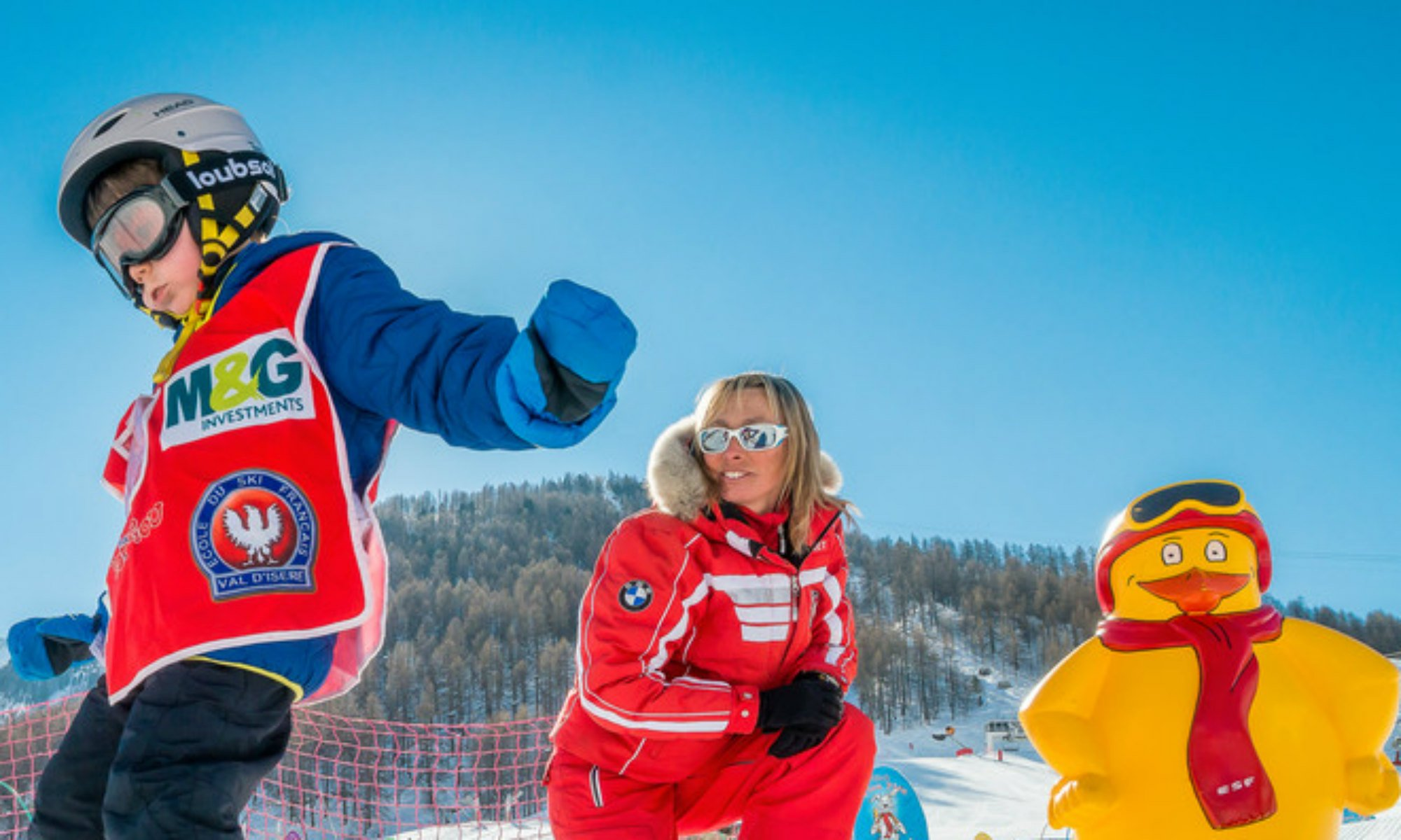 Un enfant skie sous le regard d'une monitrice de ski et la mascotte Piou Piou.
