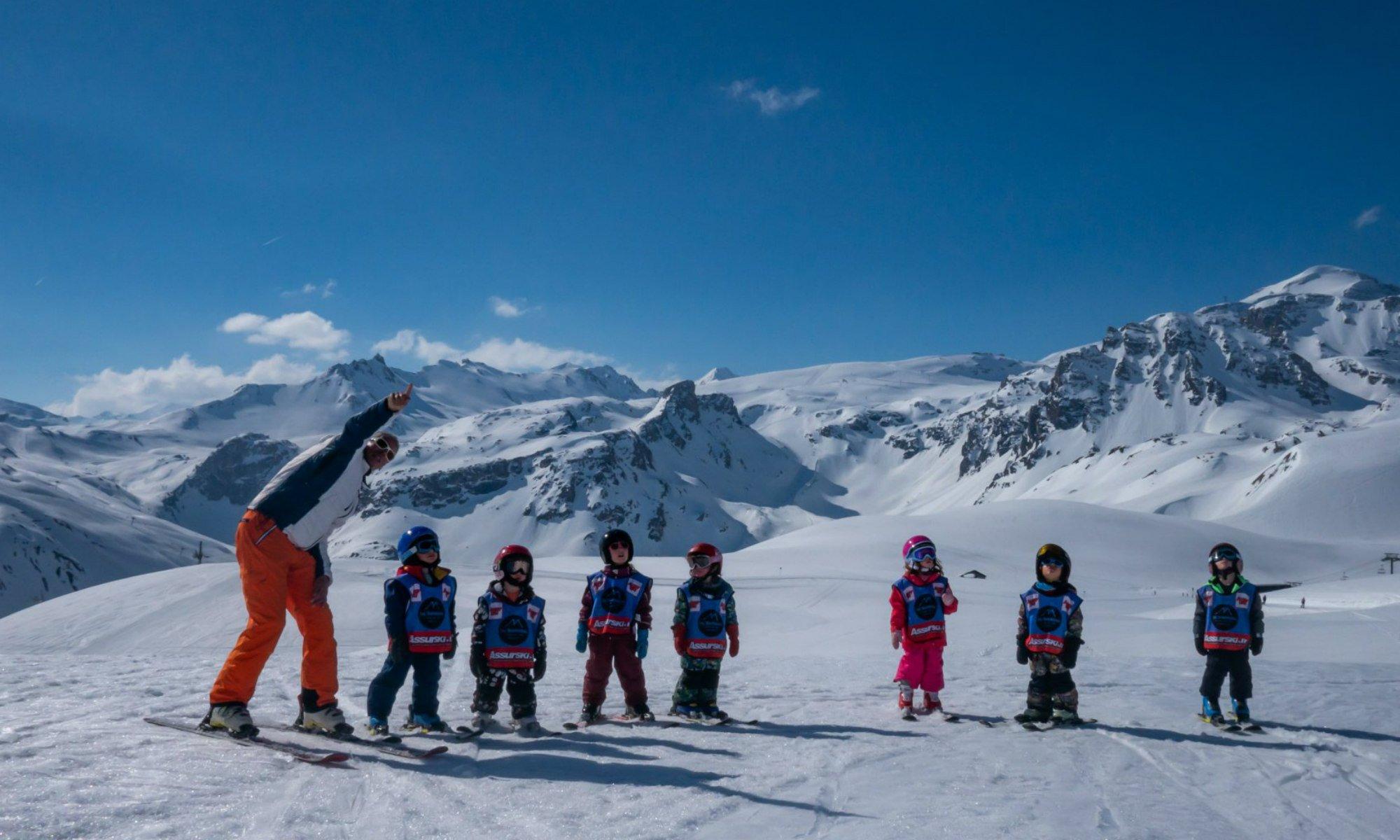 Un moniteur de ski et ses jeunes élèves sur une piste de ski.