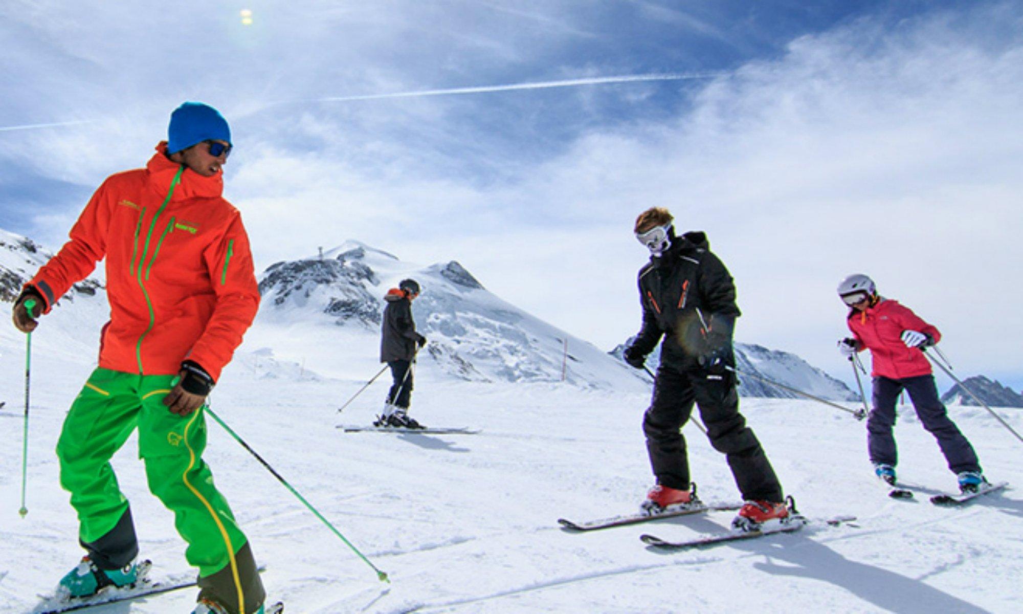 Un moniteur de ski et ses élèves adultes sur une piste enneigée.
