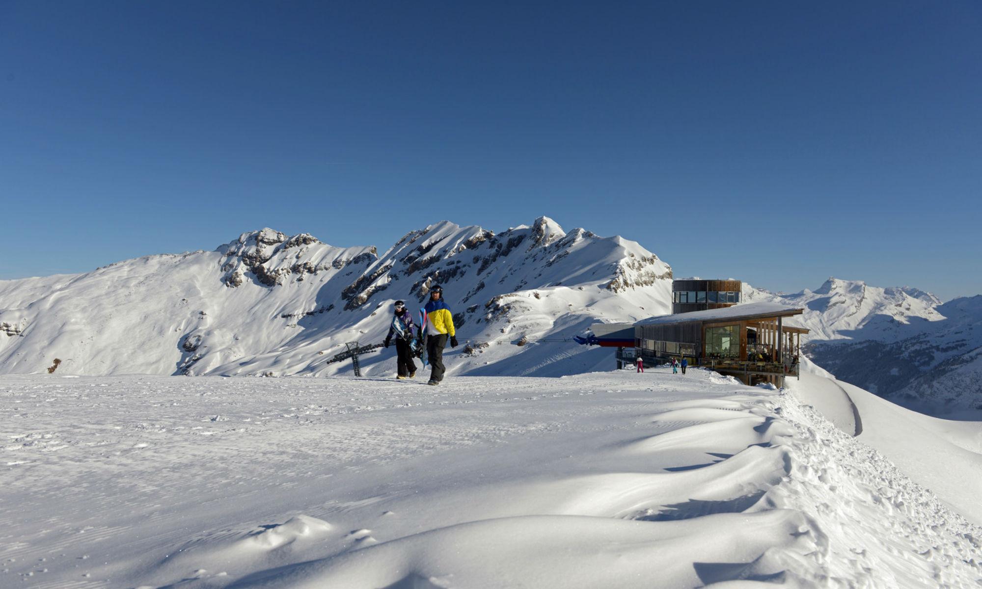 2 Erwachsene in Skiausrüstung vor einer Skiliftanlage in Meiringen-Hasliberg.