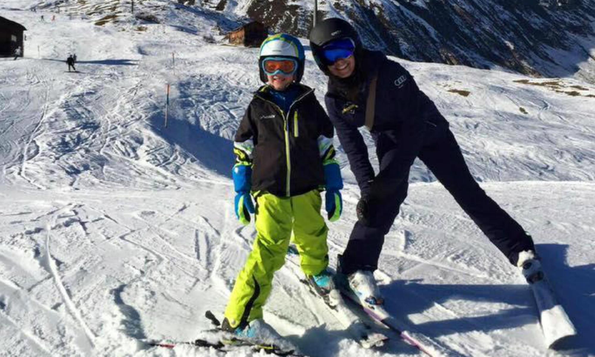Eine Skilehrerin und ein Junge stehen im Pflug auf einer Piste im Skigebiet Andermatt.
