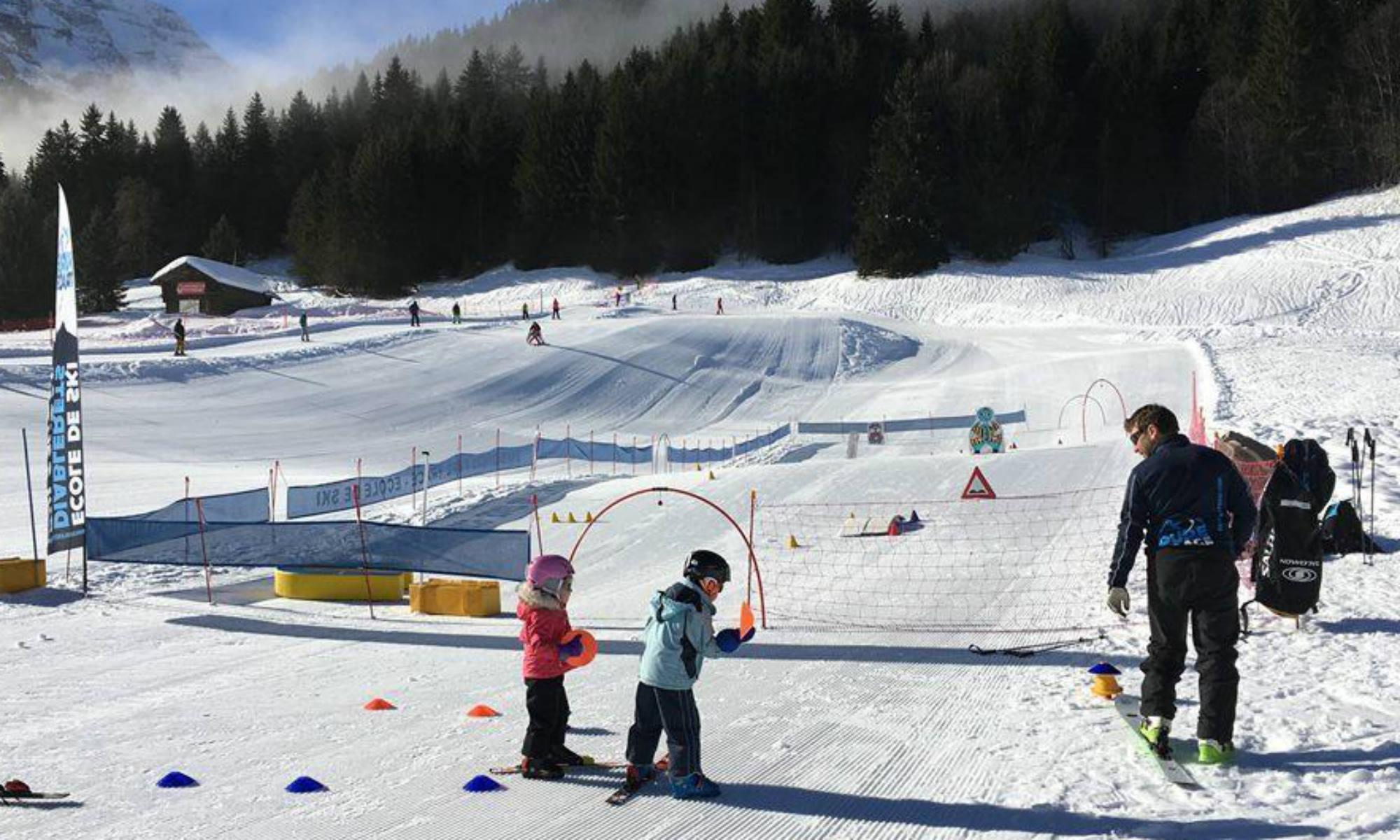 Ein Skilehrer gibt 2 Kindern Skiunterricht im Kinderland von Les Diablerets.