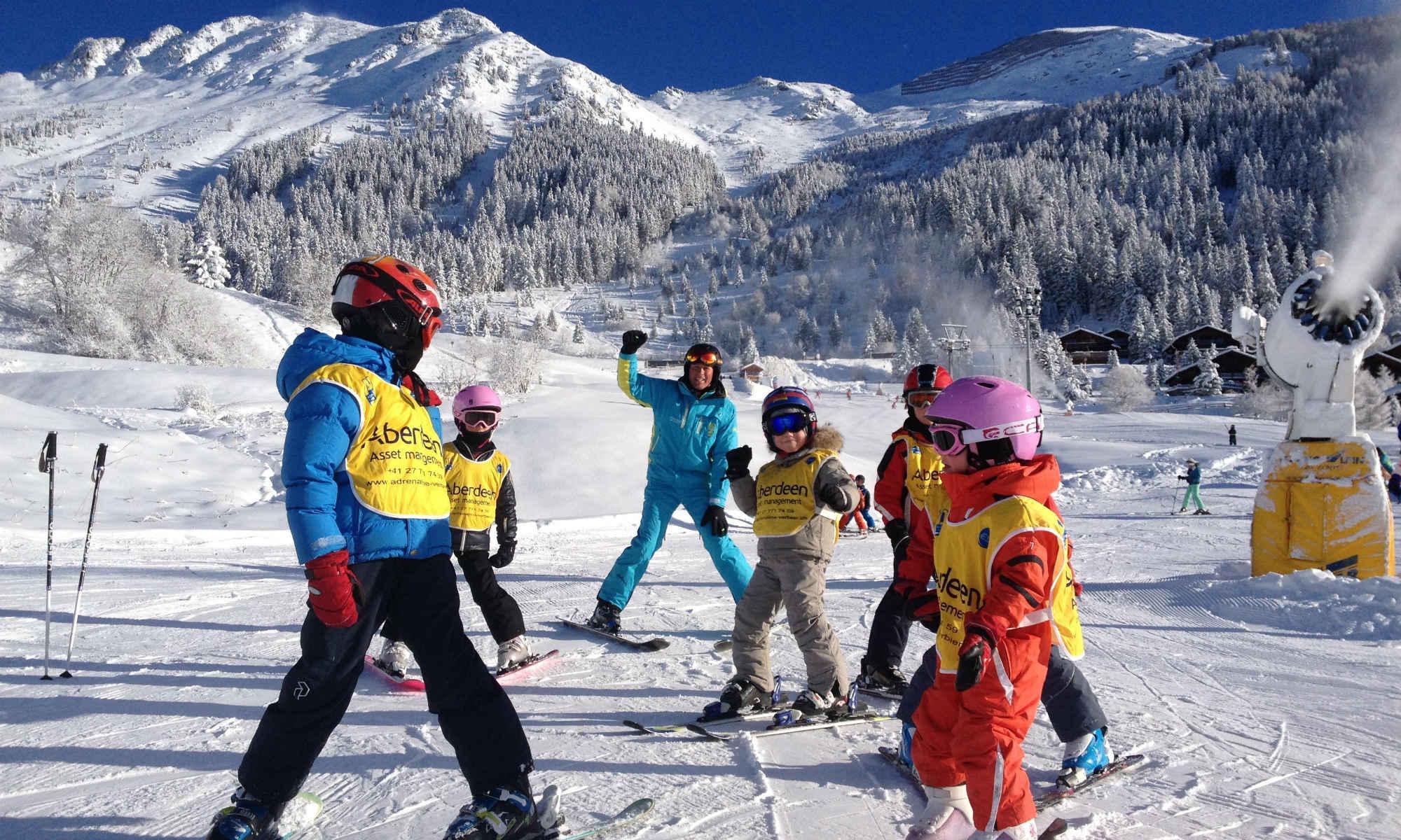 Ein Skilehrer gibt 6 Kindern Skiunterricht auf einer anfängerfreundlichen Piste im Skigebiet Verbier.