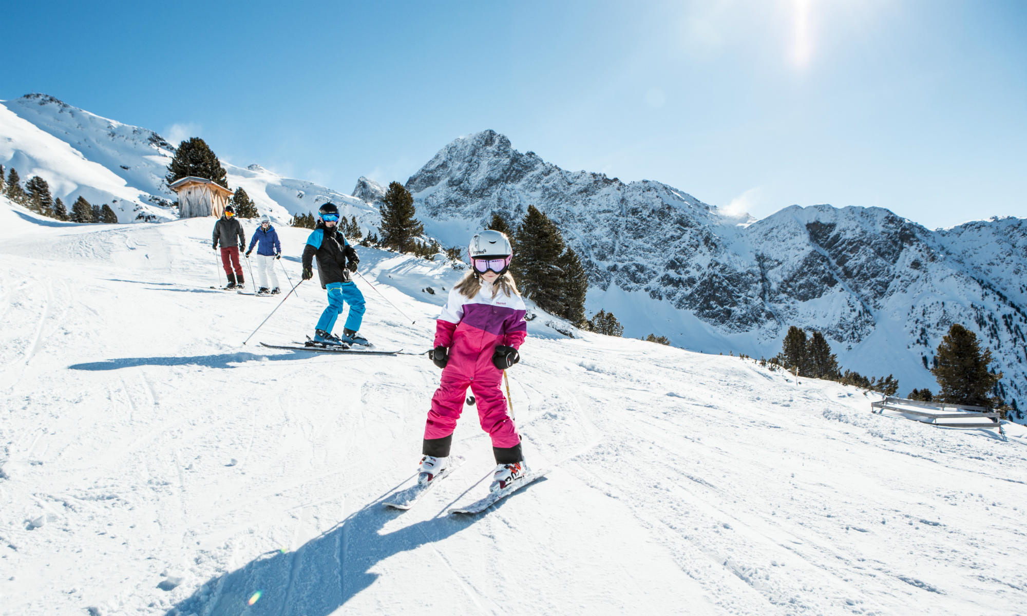 A family sliding down a sunny slope in Sölden.