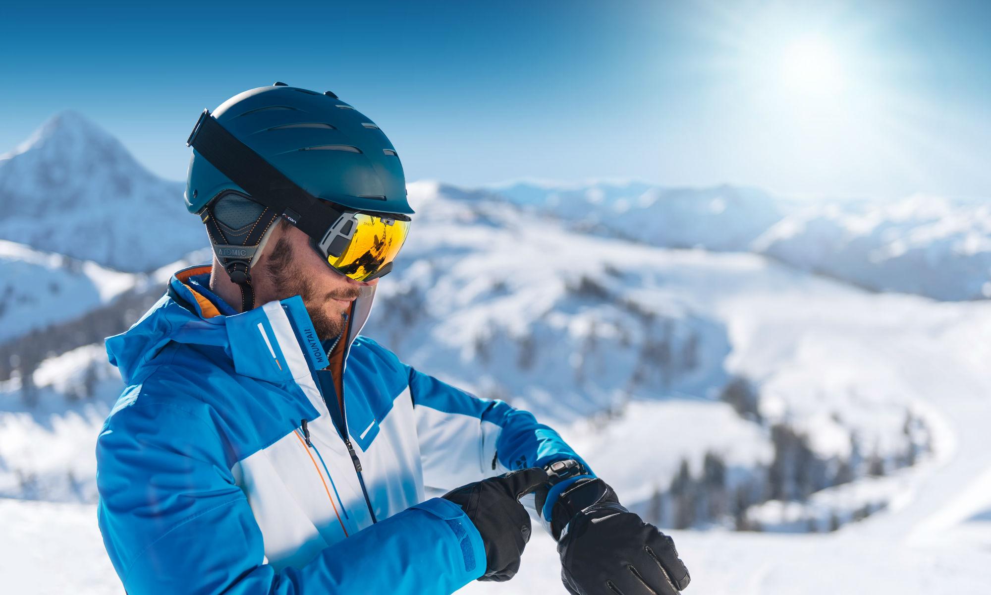 Skifahrer mit moderner Datenbrille und Smartwatch auf der Piste.