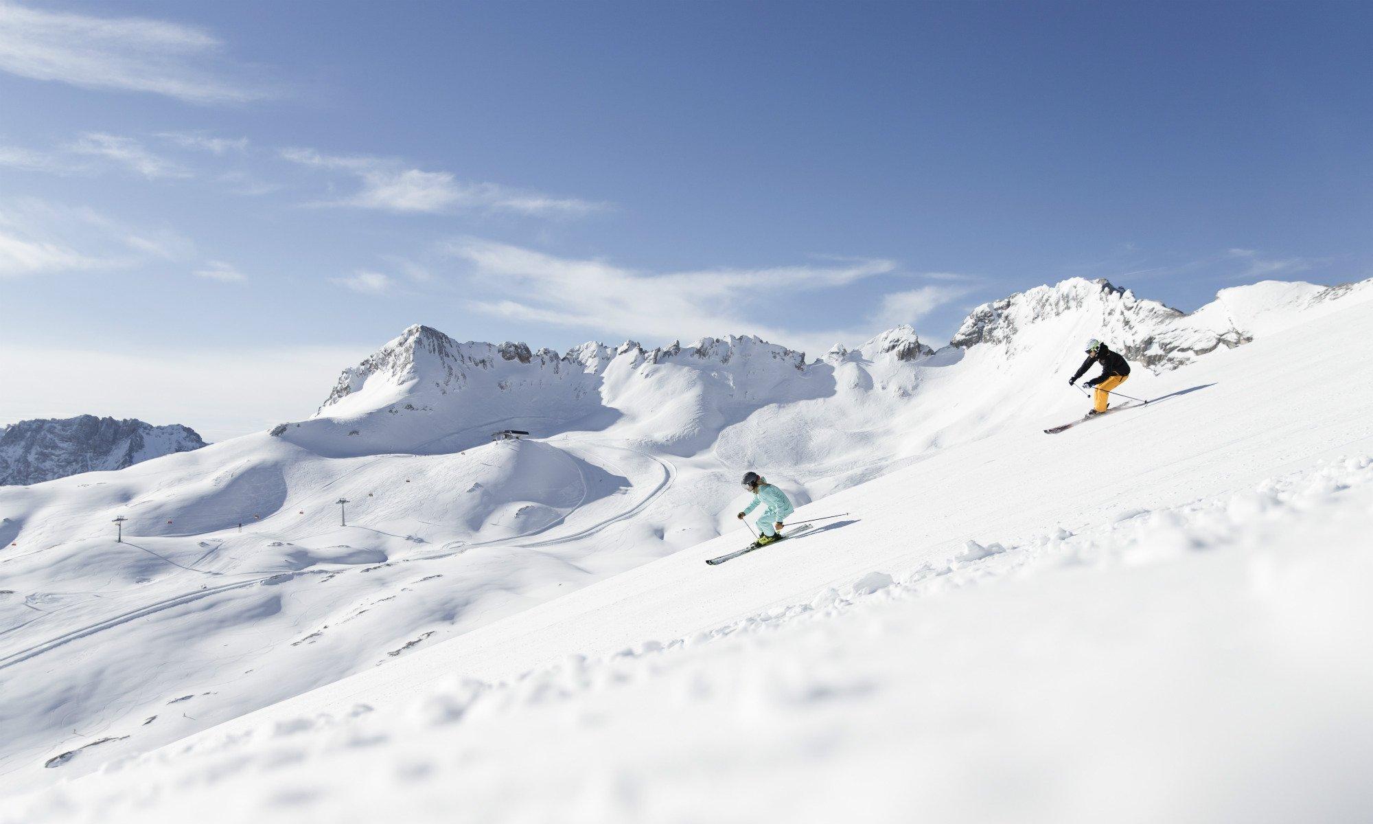 Skifahrer auf einer sonnigen Skipiste im Skigebiet Zugspitze bei Garmisch-Partenkirchen.