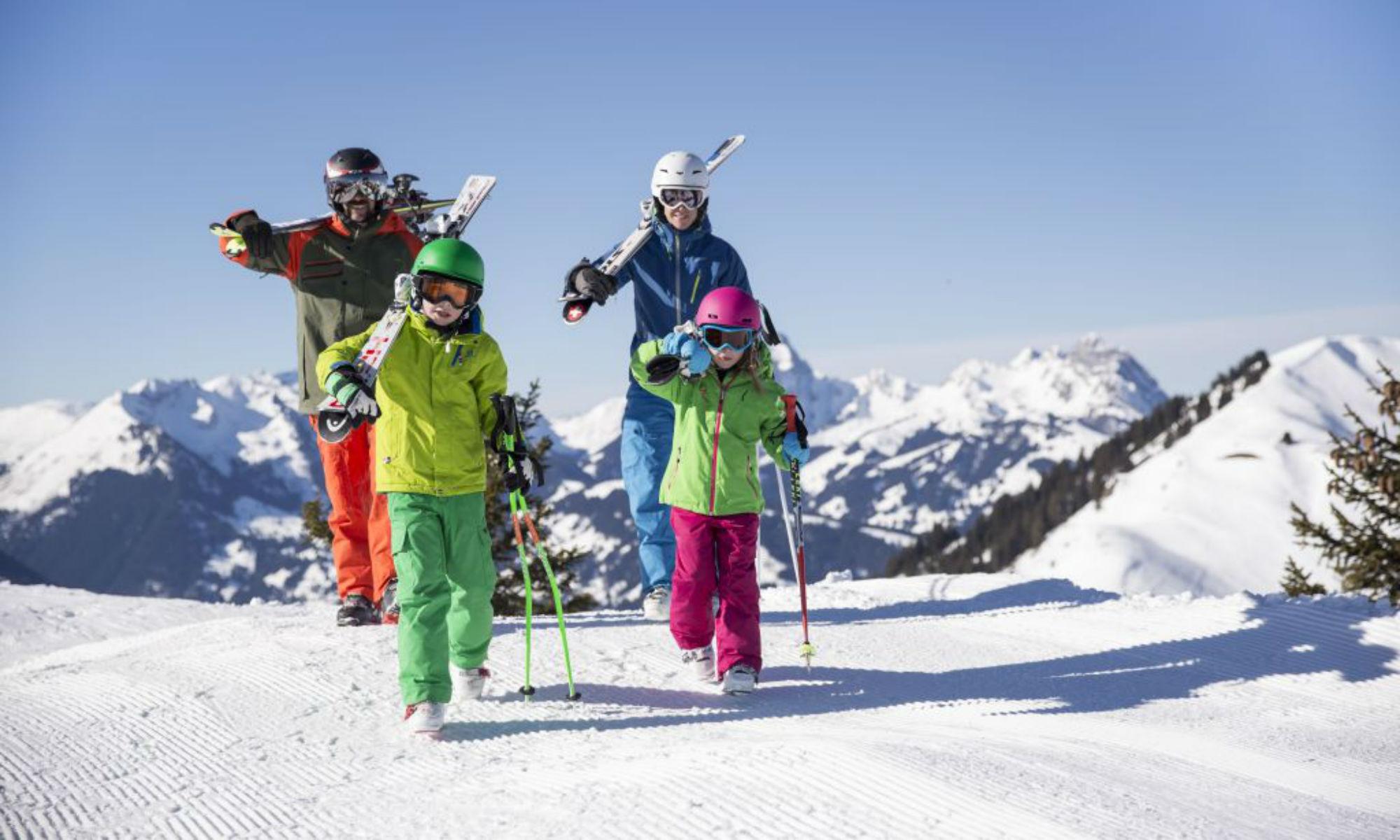 Eine Familie beim Tragen der Skiausrüstung auf einer sonnigen Piste in Gstaad-Saanen.