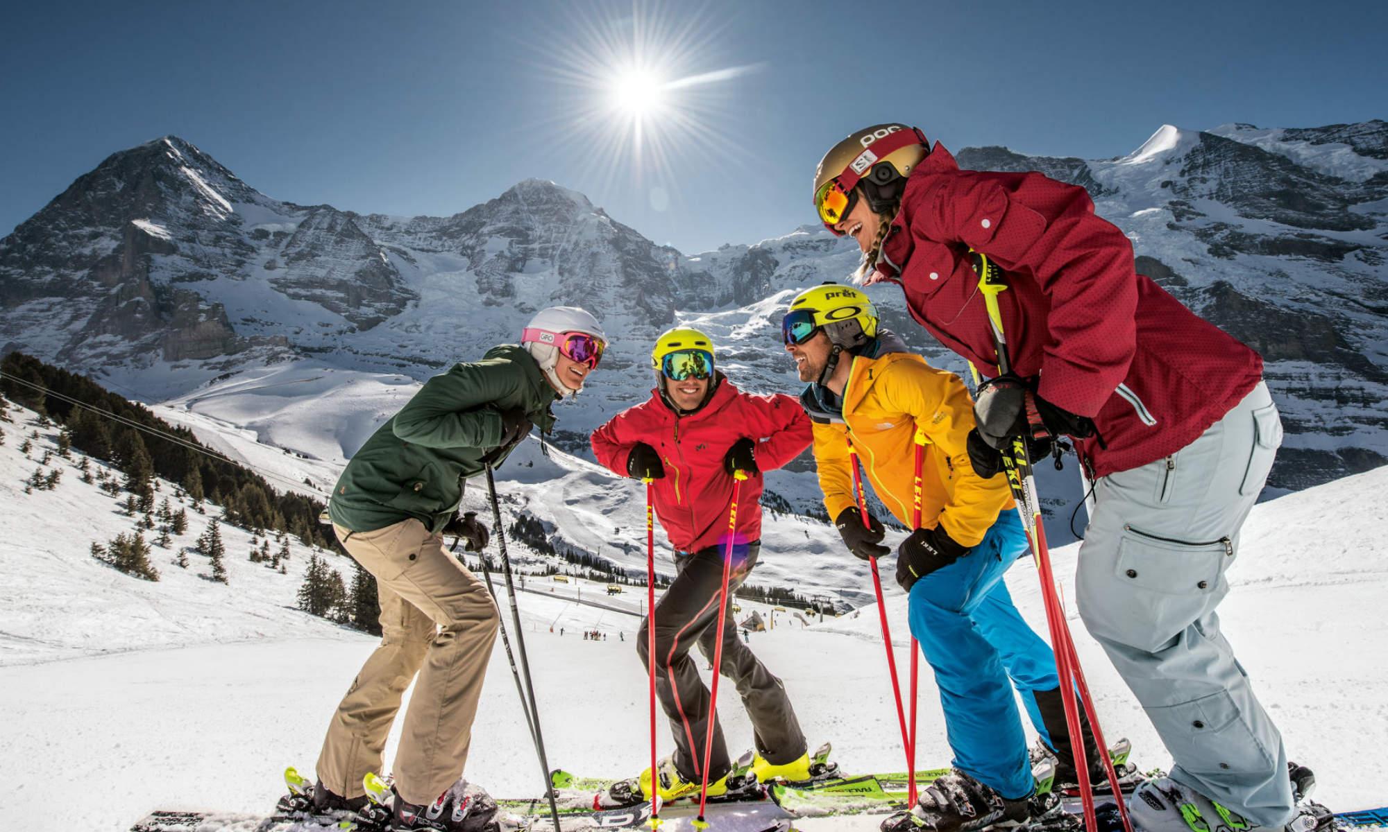 4 gutgelaunte Skifahrer auf einer Skipiste der Jungfrau Skiregion.