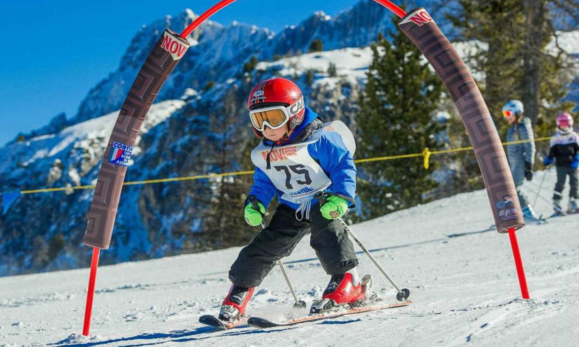 Ein Kind fährt durch einen bunten Bogen auf einer Übungsfläche im Skigebiet Cortina d'Ampezzo.