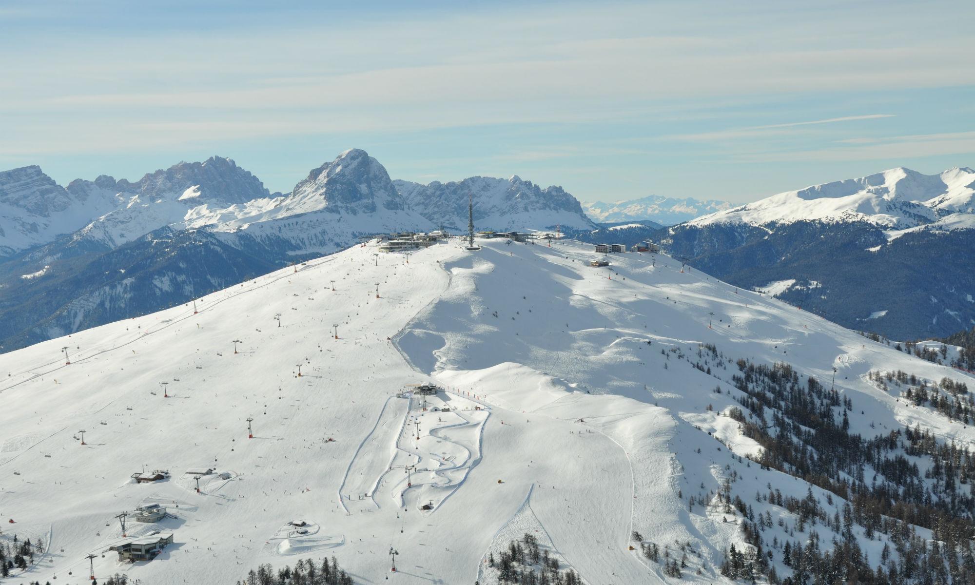 Sonnige Pisten am Kronplatz mit einem Rundum-Panorama auf die Dolomiten.