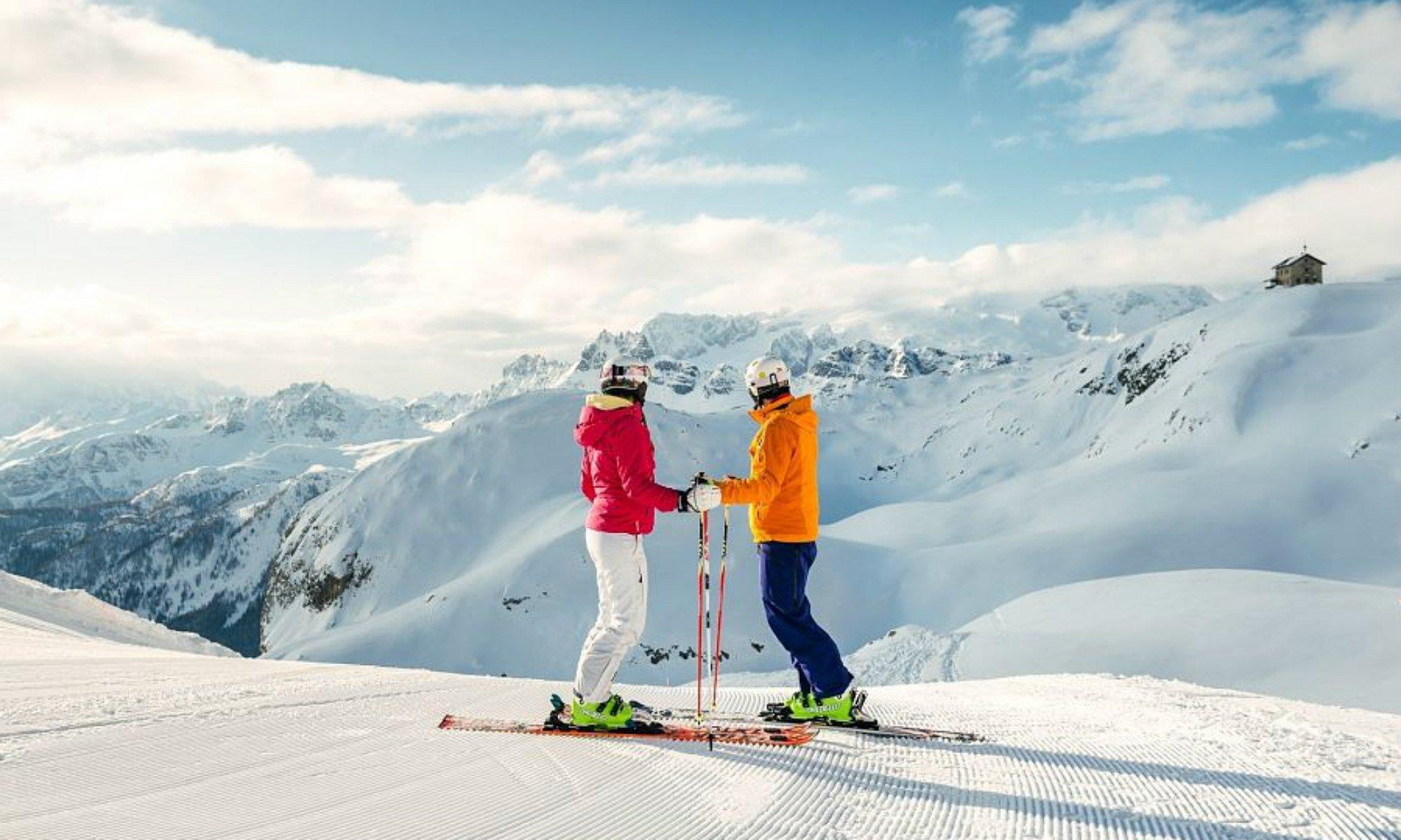 Zwei Skifahrer auf einer sonnigen Piste im Skigebiet La Villa blicken auf die umliegenden Berggipfel der Dolomiten.