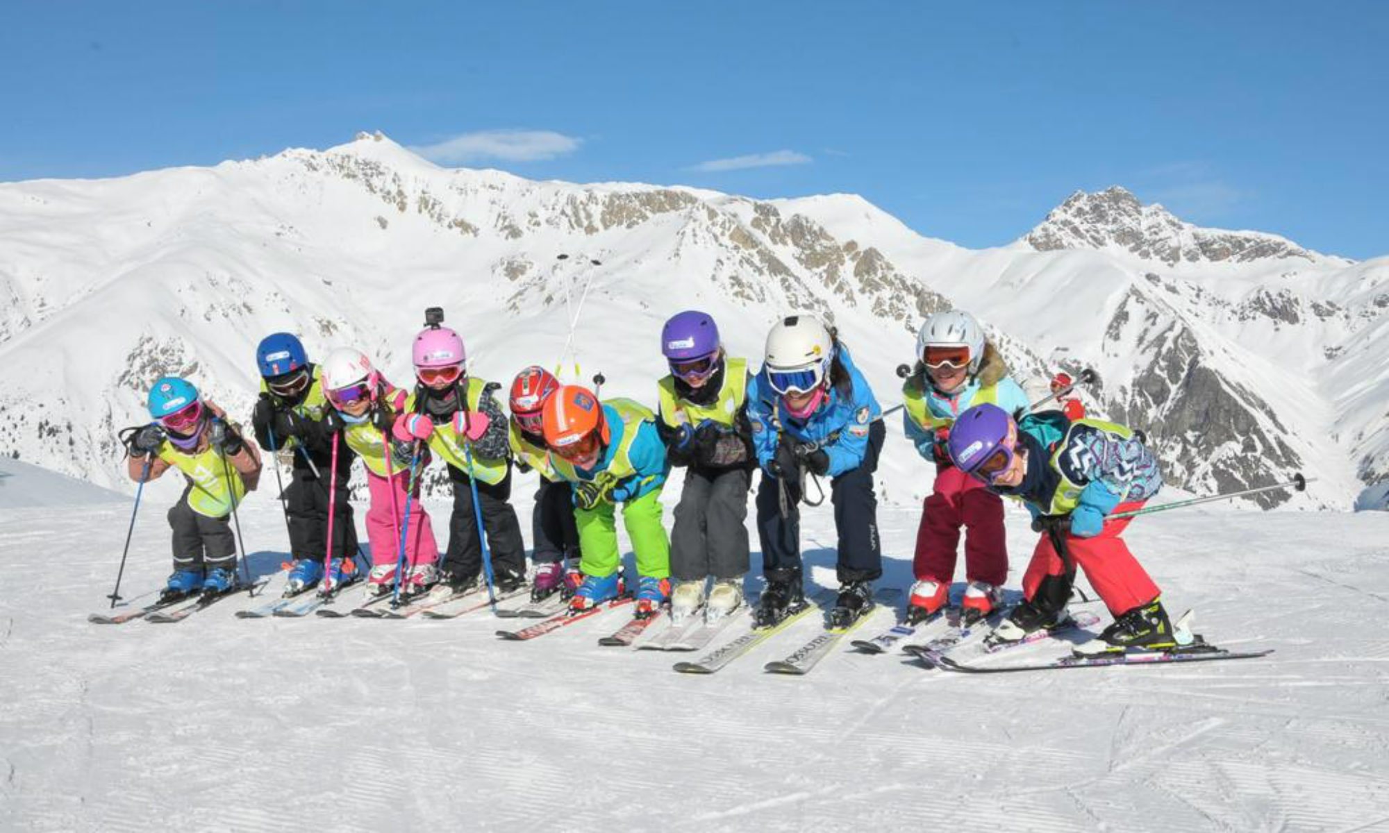 Eine fröhliche Kindergruppe beim Skikurs im Skigebiet Livigno.