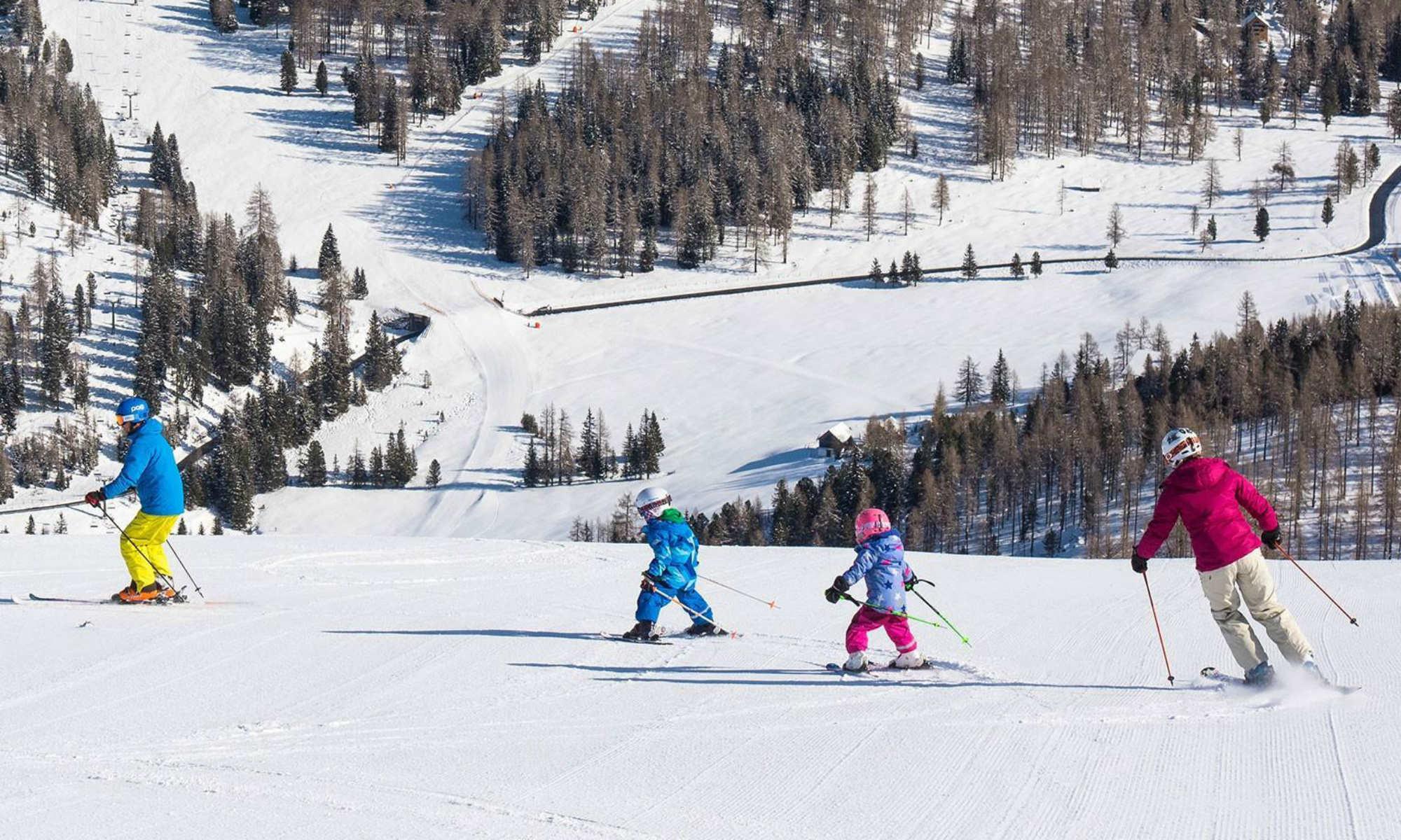 Kinder und Erwachsene beim Skikurs auf einer sonnigen Piste im Skigebiet Hochrindl.