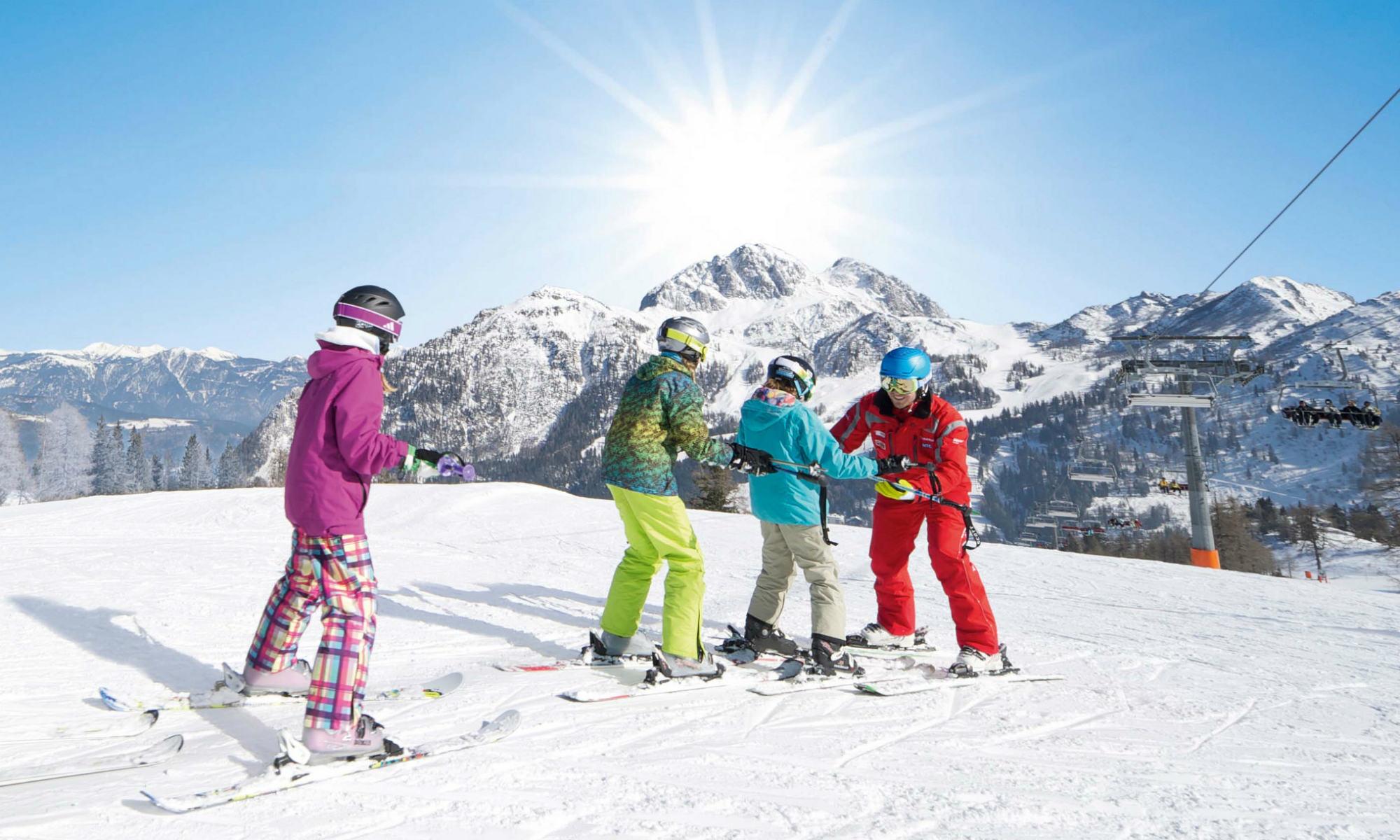 Drei Teenager beim Skikurs auf einer sonnigen Piste im Skigebiet Nassfeld.