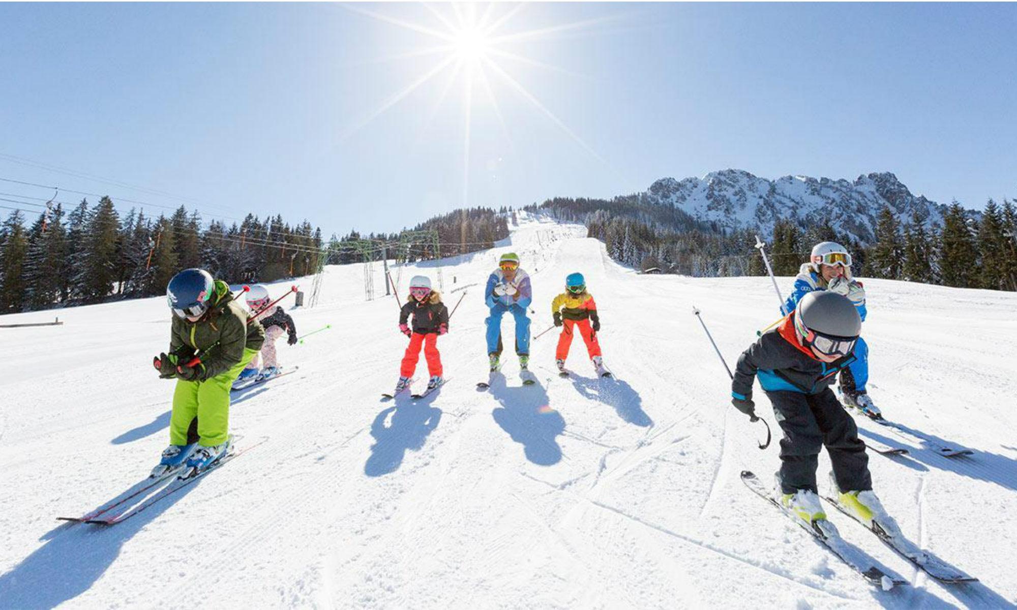 Eine Skikursgruppe befährt eine sonnige blaue Piste in Balderschwang.