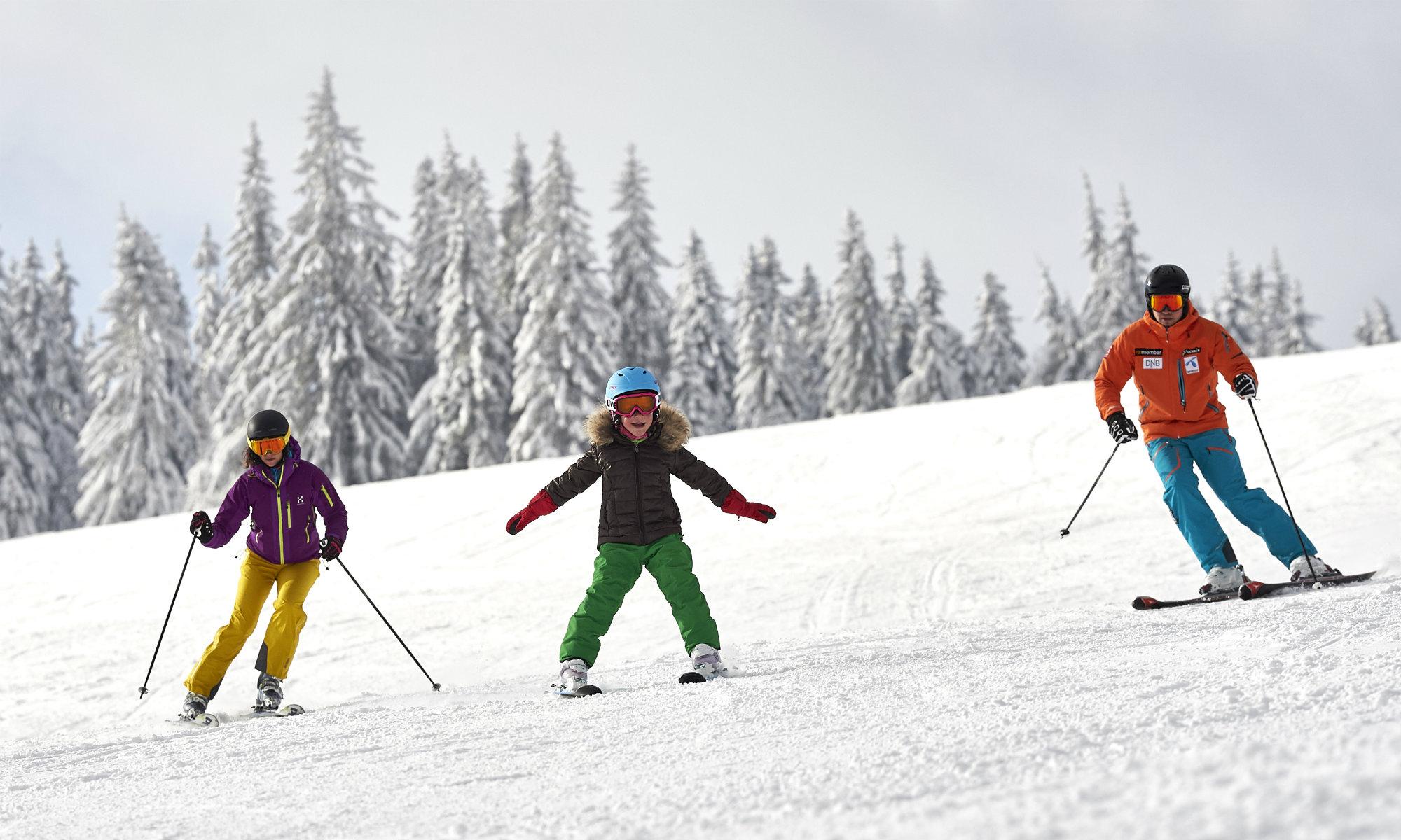 Eine Familie übt das Skifahren auf einer blau markierten Piste am Großen Arber.