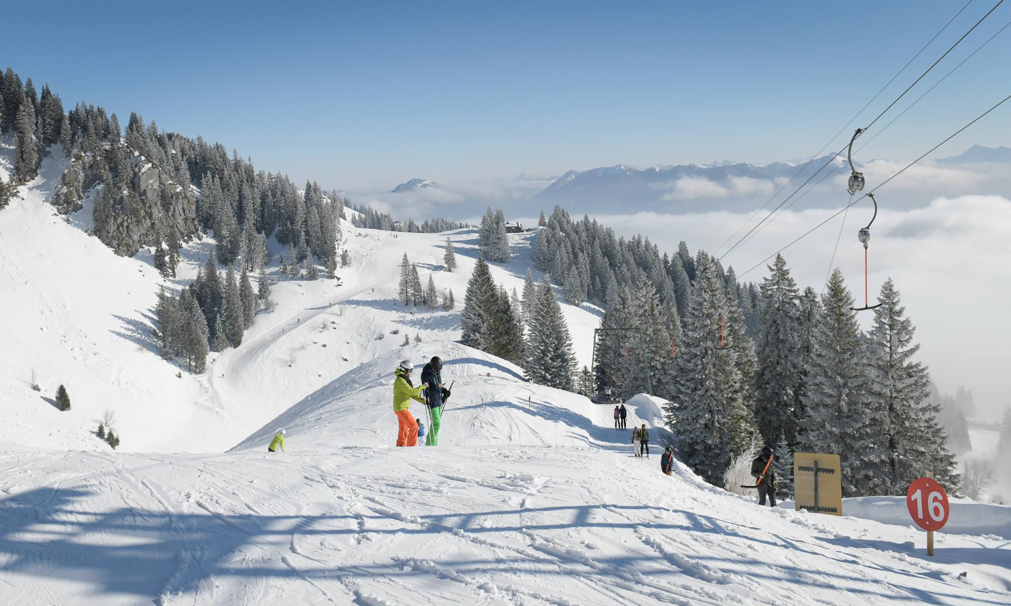 Zwei Skifahrer beim Liftfahren auf einer sonnigen Piste im Skigebiet Brauneck-Lenggries.