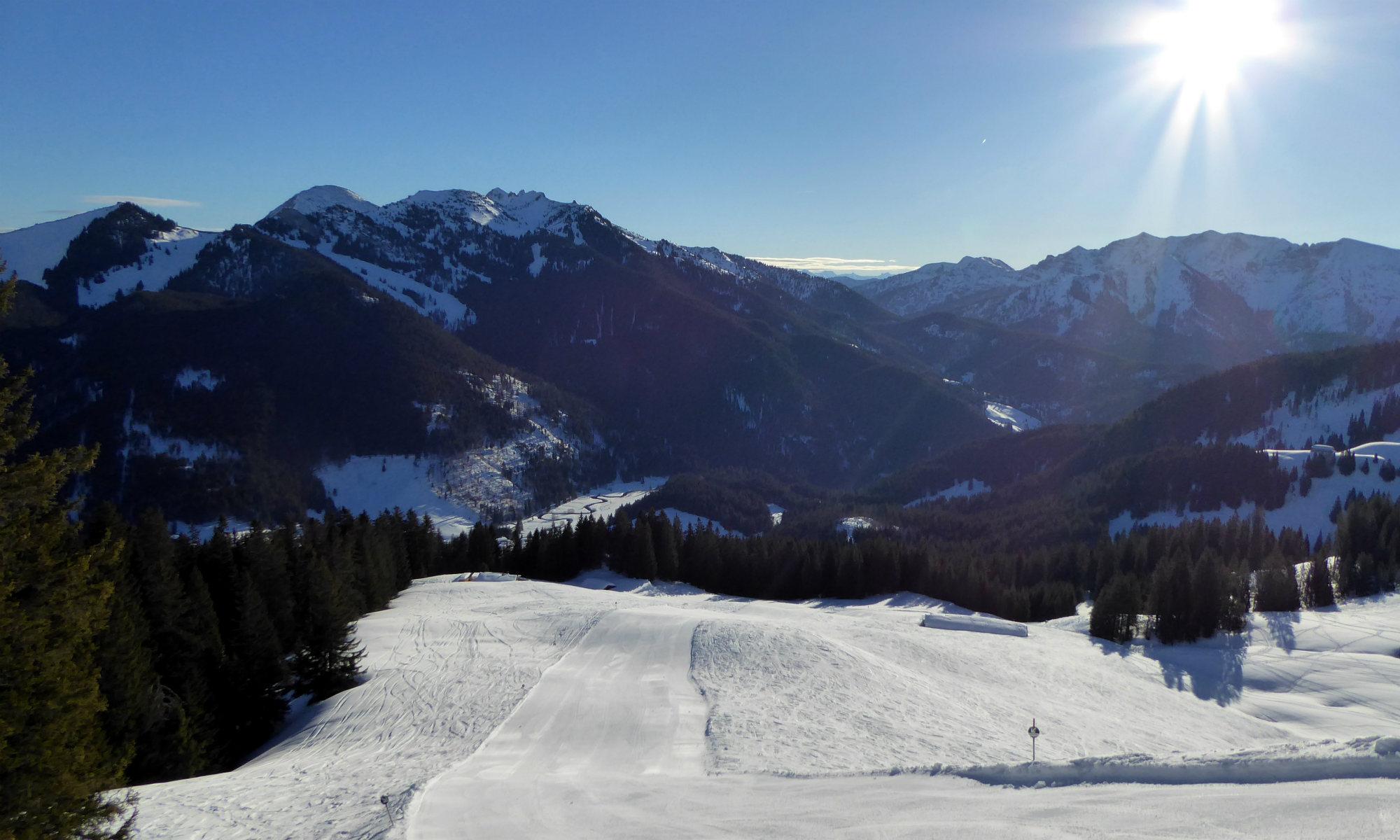 Von den Gipfeln des Skigebiets Tegernsee hat man eine wunderschöne Aussicht auf die sonnigen, schneebedeckten Pisten.