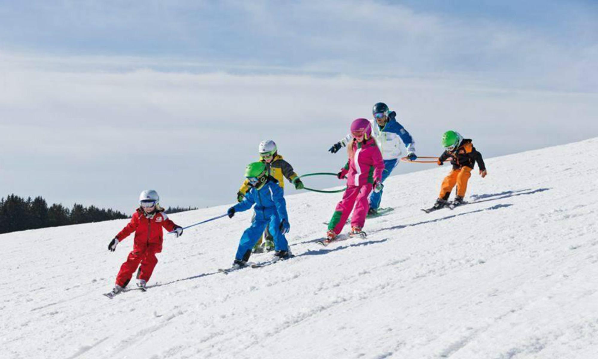 Kinder üben das Skifahren in Kleingruppen mit bunten Reifen auf einer Piste im Skigebiet Sudelfeld.