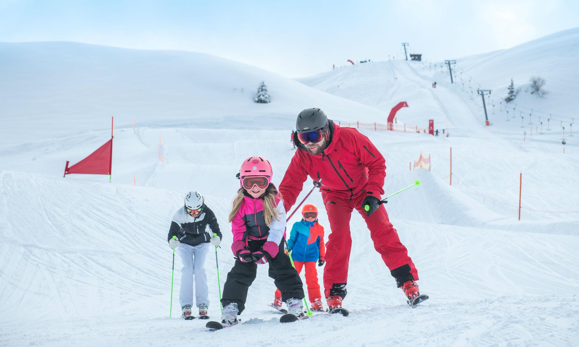 Ein Skilehrer, 2 Kinder und eine Erwachsene beim Skikurs in Kitzbühel.