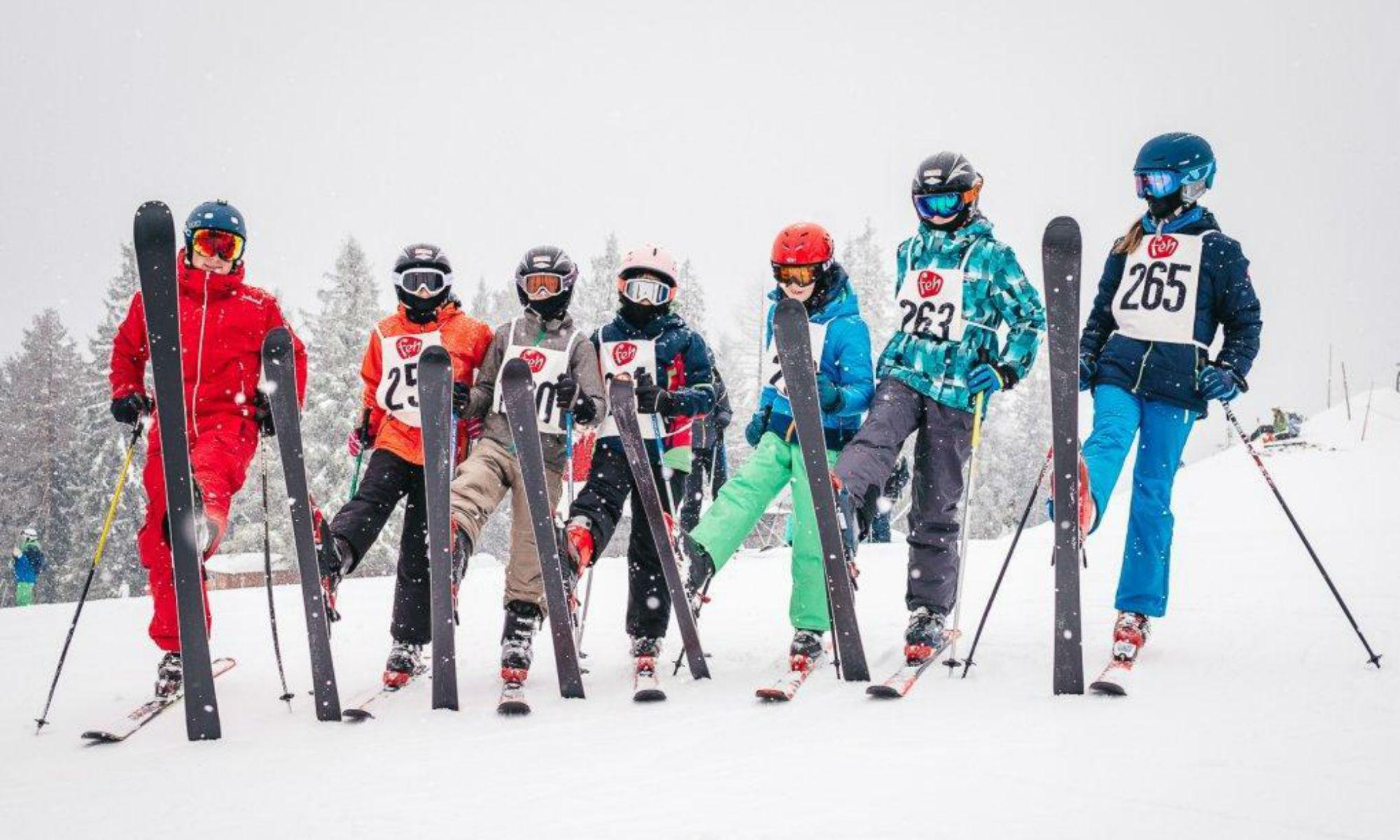 Ein Skilehrer und 6 Kinder posieren mit aufgestellten Skiern auf einer Piste der Mariazeller Bürgeralpe.