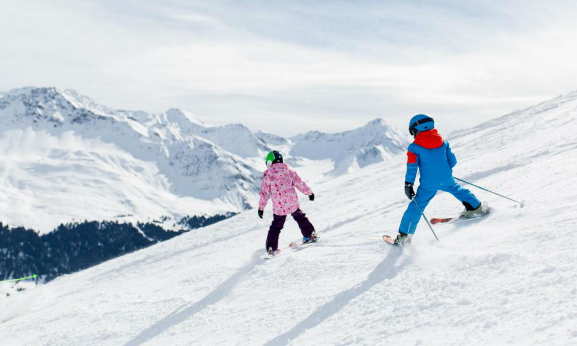 2 Kinder beim Üben des Schneepflugs auf einer sonnigen Piste im Skigebiet Arosa.