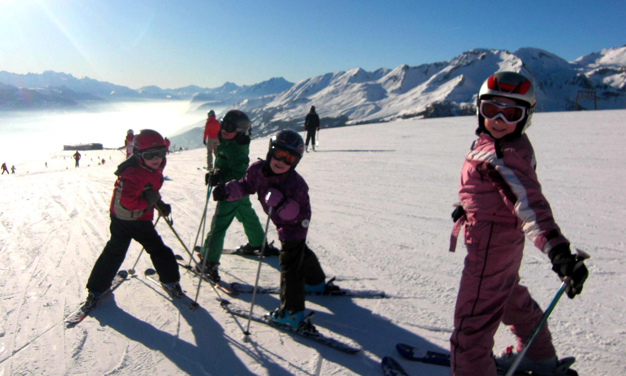 4 fröhliche Kinder beim Skifahren lernen auf einer sonnigen Piste im Skigebiet Crans-Montana.