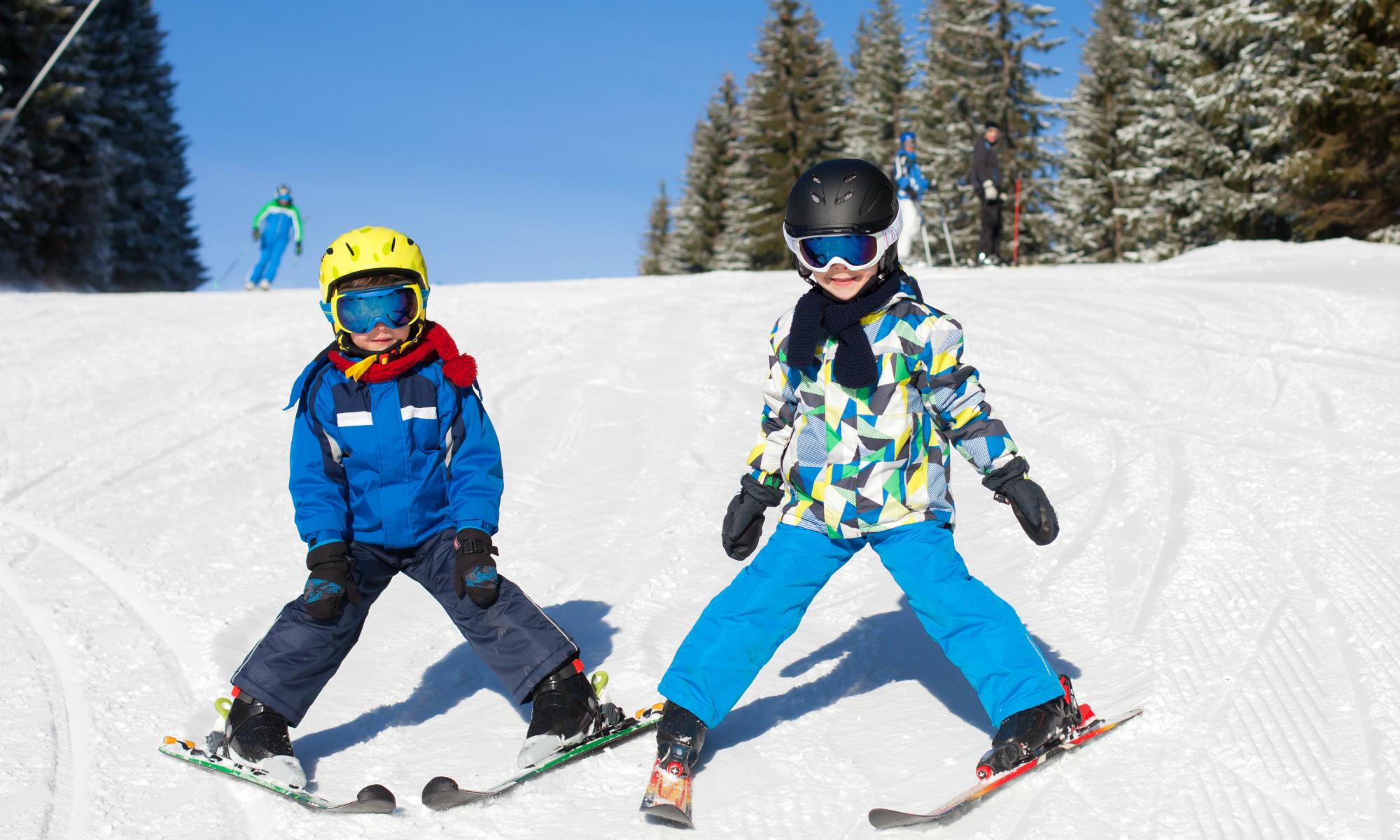 Zwei Kinder beim Schneepflug fahren auf einer sonnigen Skipiste.