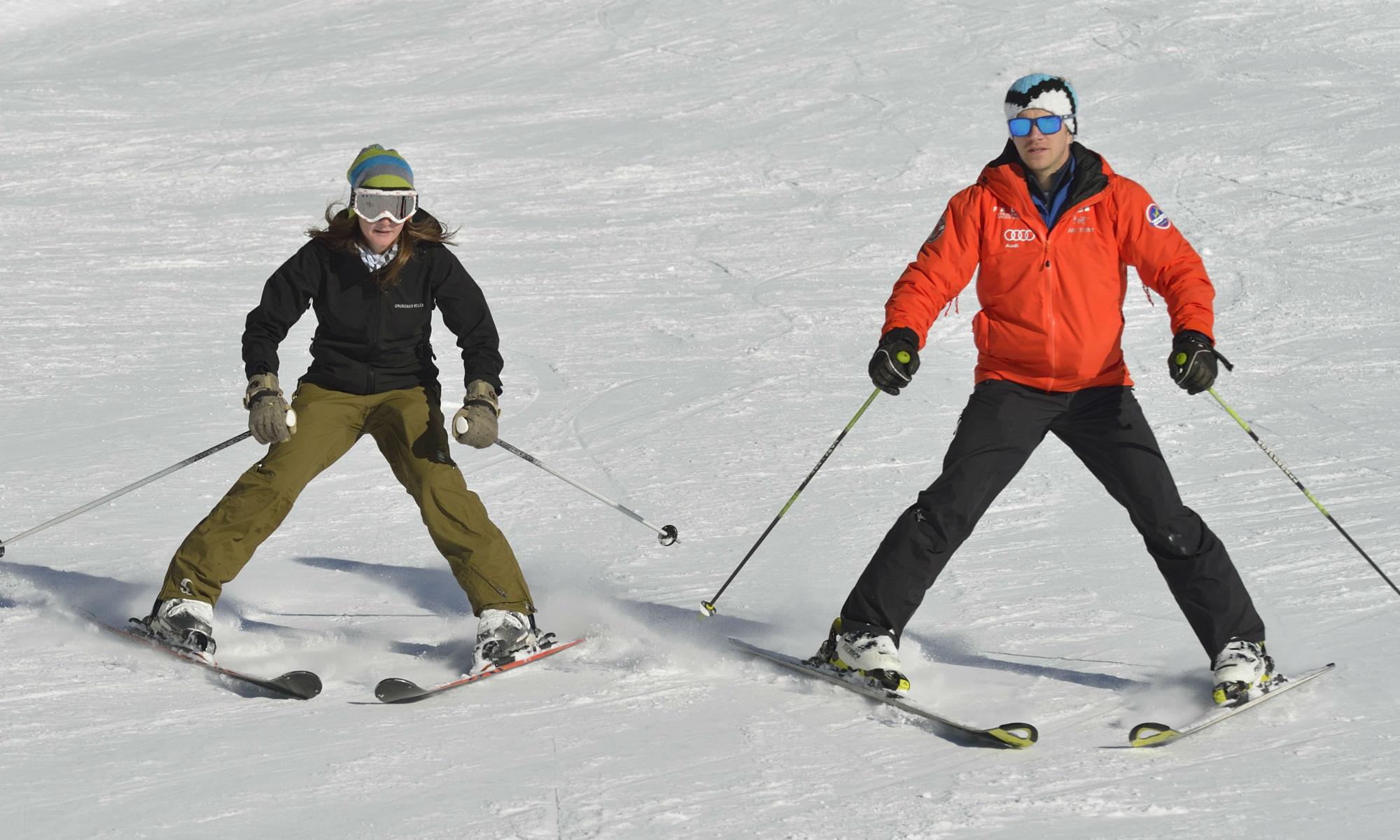 Skilehrer und -schülerin beim Üben des Pflugs auf einer Skipiste.