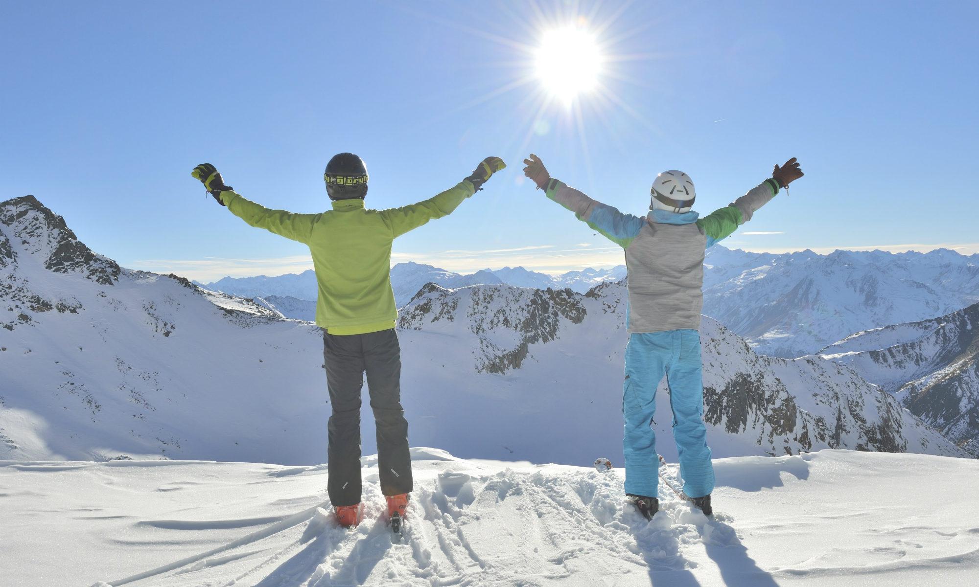 Zwei Skifahrer blicken von einer Skipiste auf sonnige Berggipfel.
