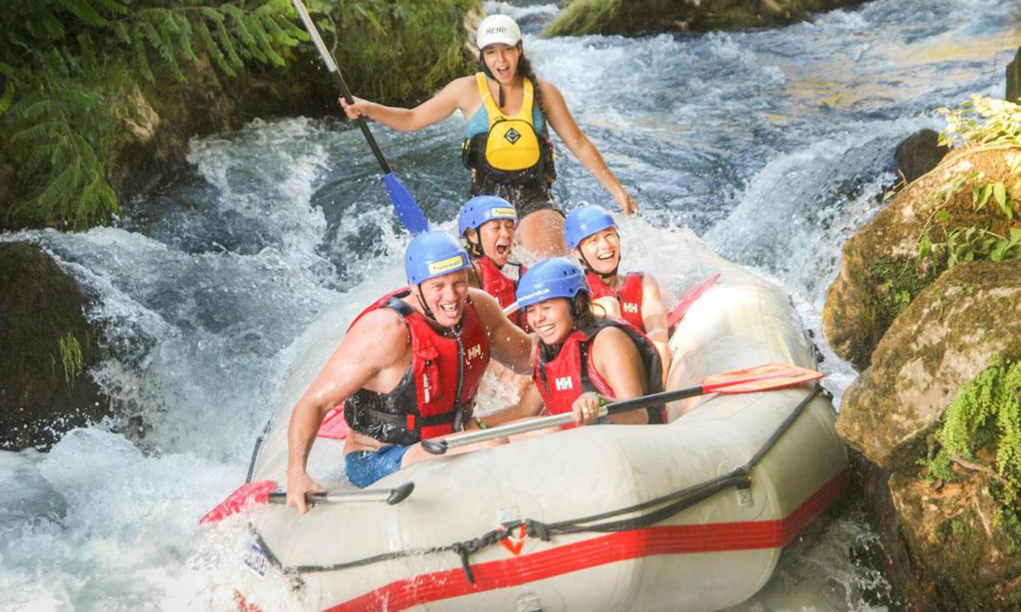 Un gruppo di persone si trova all'inizio di una grotta durante il rafting in Croazia.