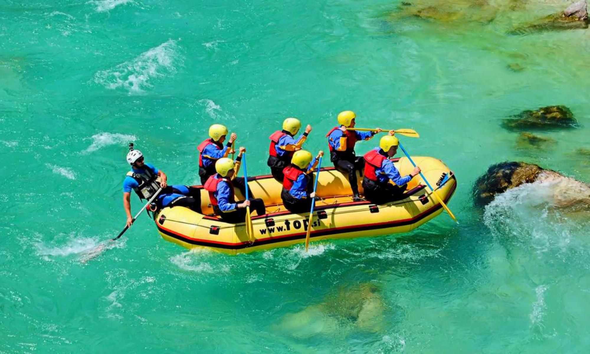 Un gruppo sta facendo rafting sull'Isonzo. La colorazione dell'acqua è di un verde intenso.