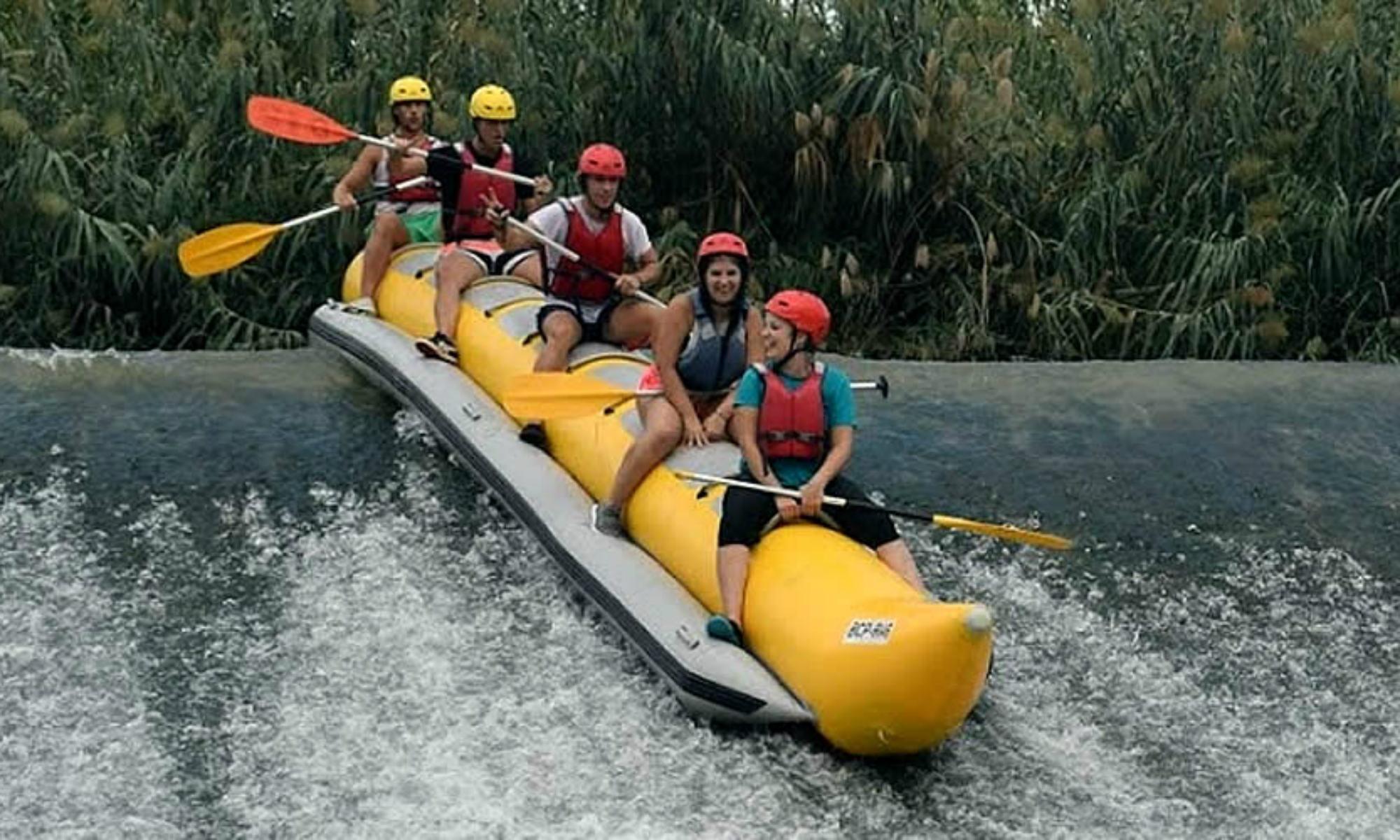 Un gruppo di ragazzi fanno rafting su una banana boat.