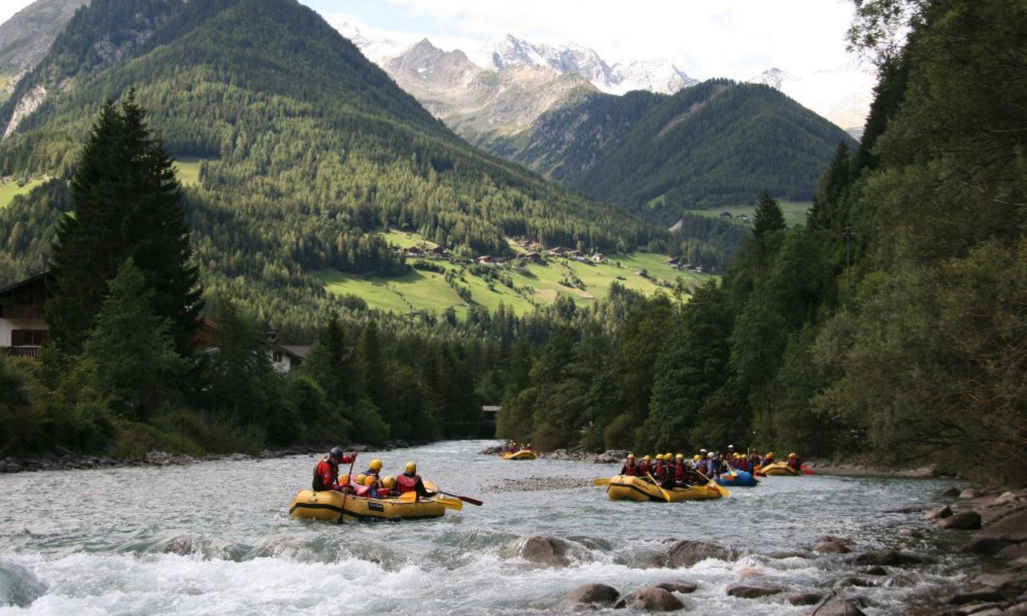 Mehrere Rafts paddeln auf einem Wildfluss in Südtirol vor dem Bergpanorama der Dolomiten.