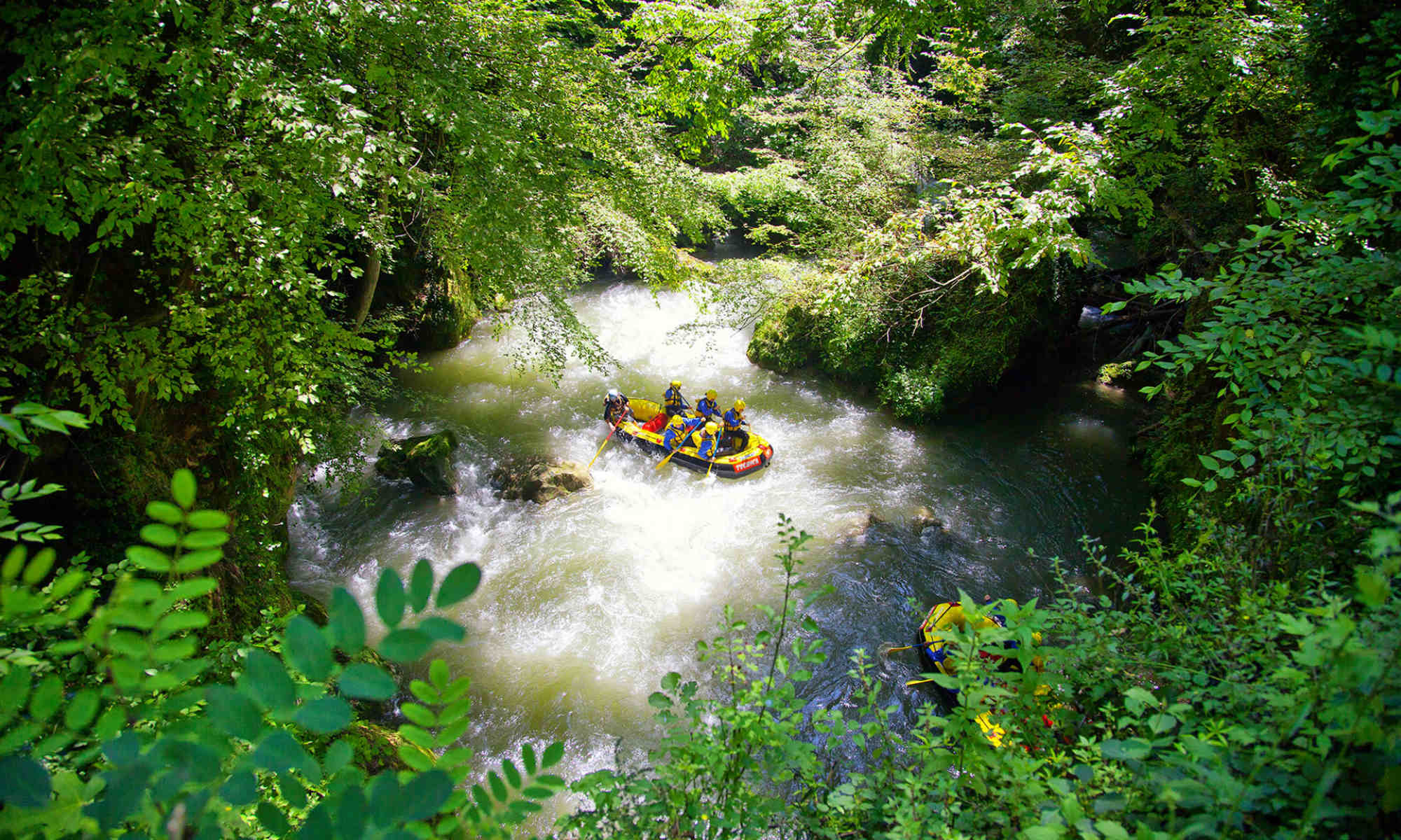 Due barche immerse nel verde scendono il fiume durante il rafting in Italia.