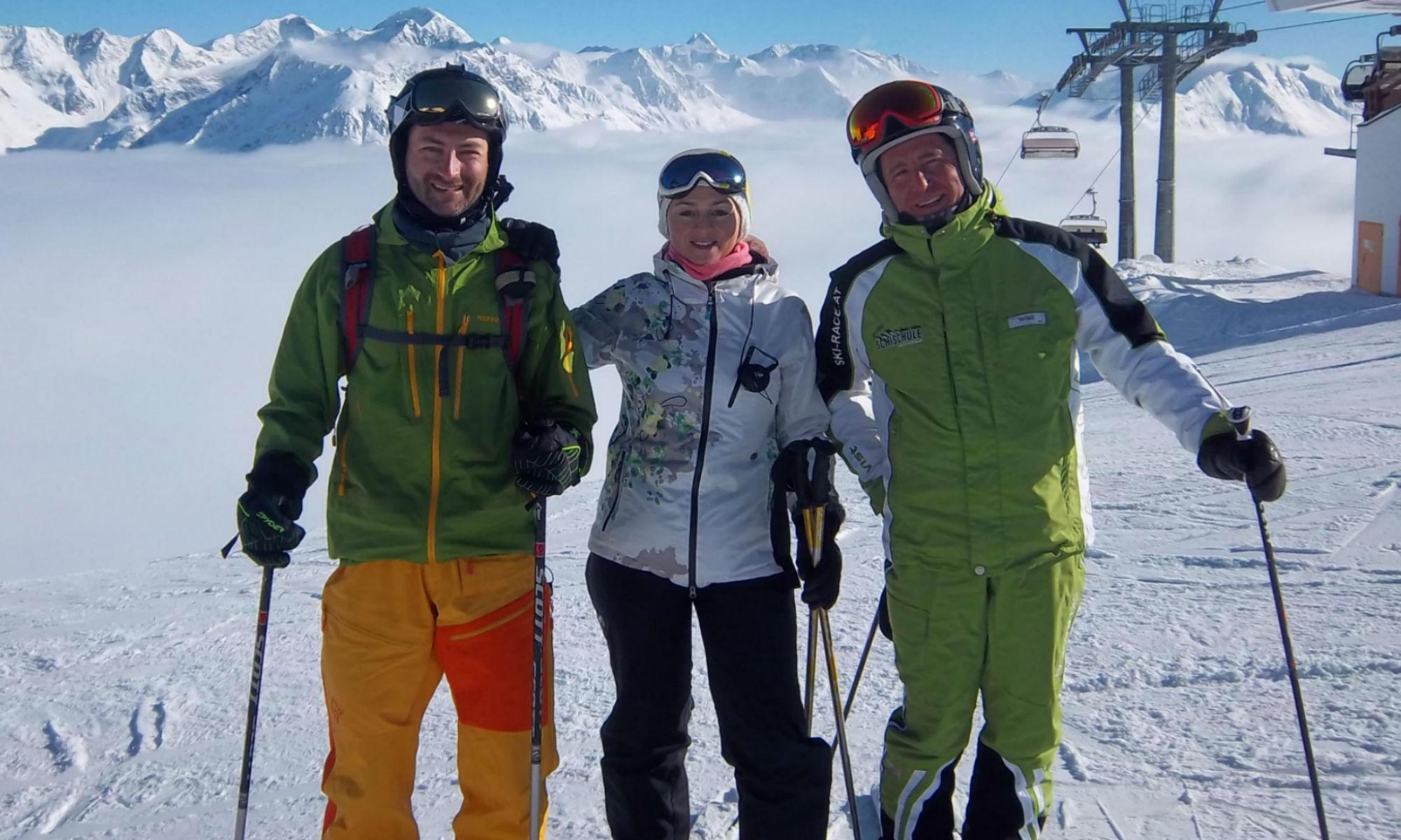 2 Skikurs Teilnehmer zusammen mit einem Skilehrer auf einer sonnigen Piste in Sölden.