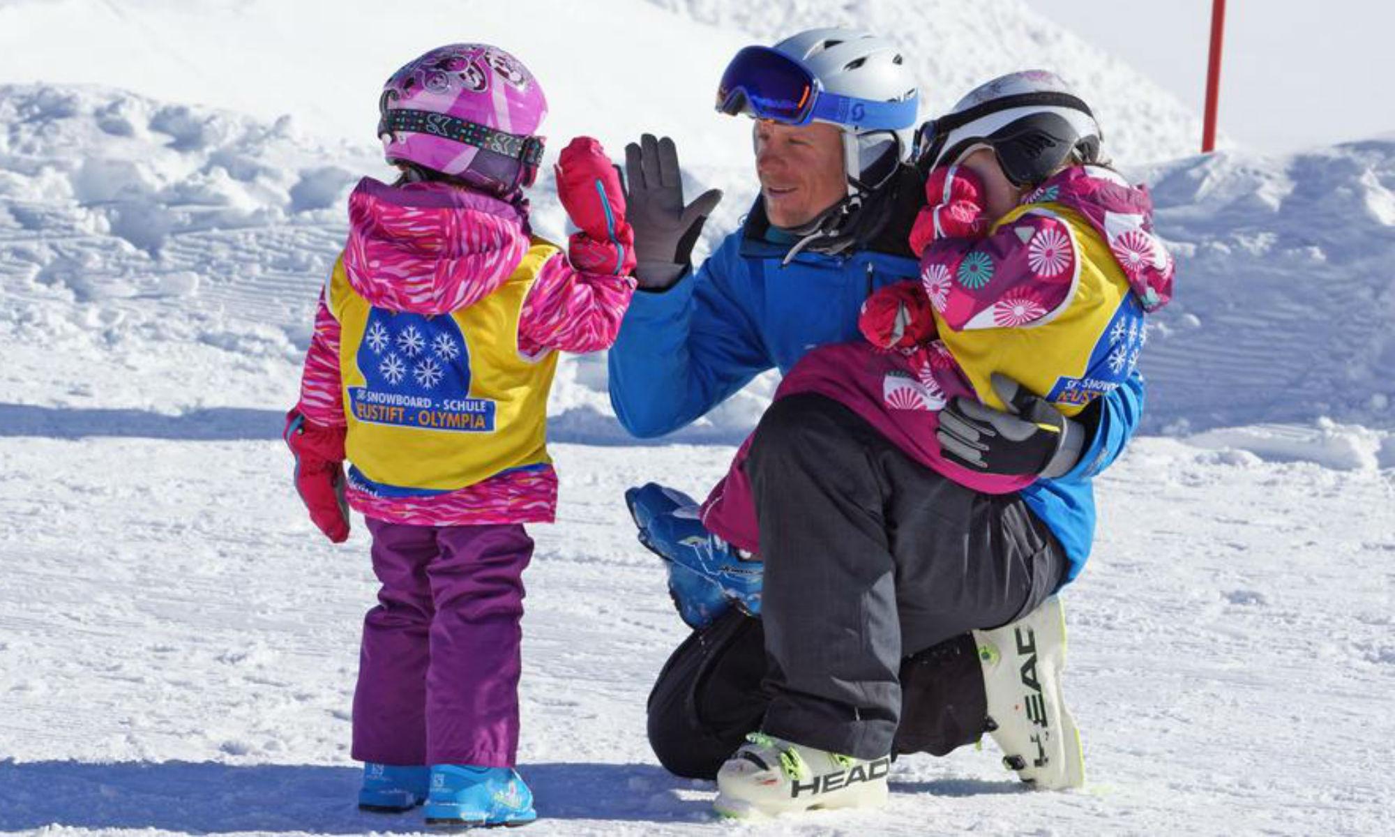 Ein Skilehrer klatscht mit einem Kind auf einer sonnigen Piste am Stubaier Gletscher ab, während er ein zweites Kind im Arm hält.