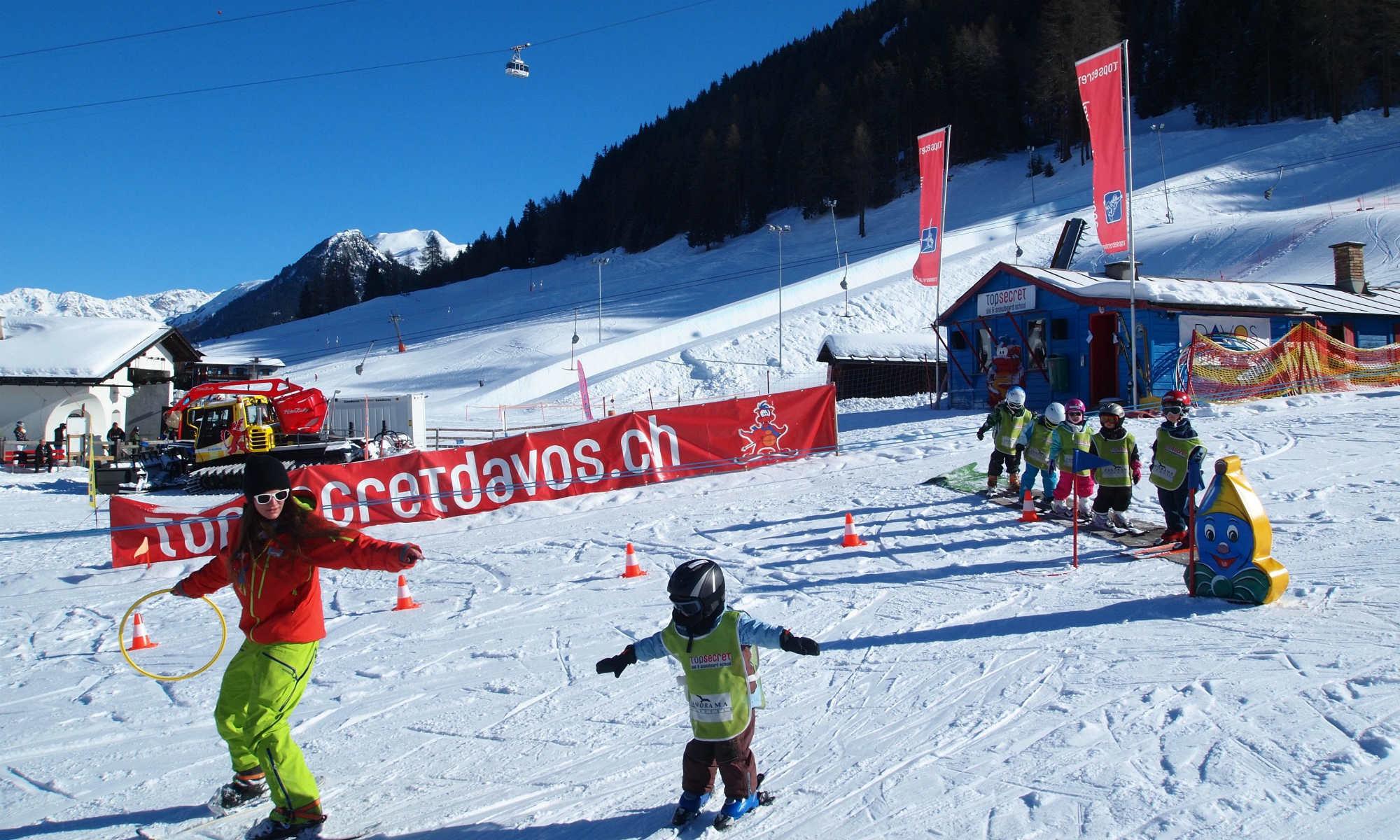 Eine Skilehrerin übt mit mehreren Kindern die Skitechnik in einem Kinderland im Skigebiet Davos Klosters.