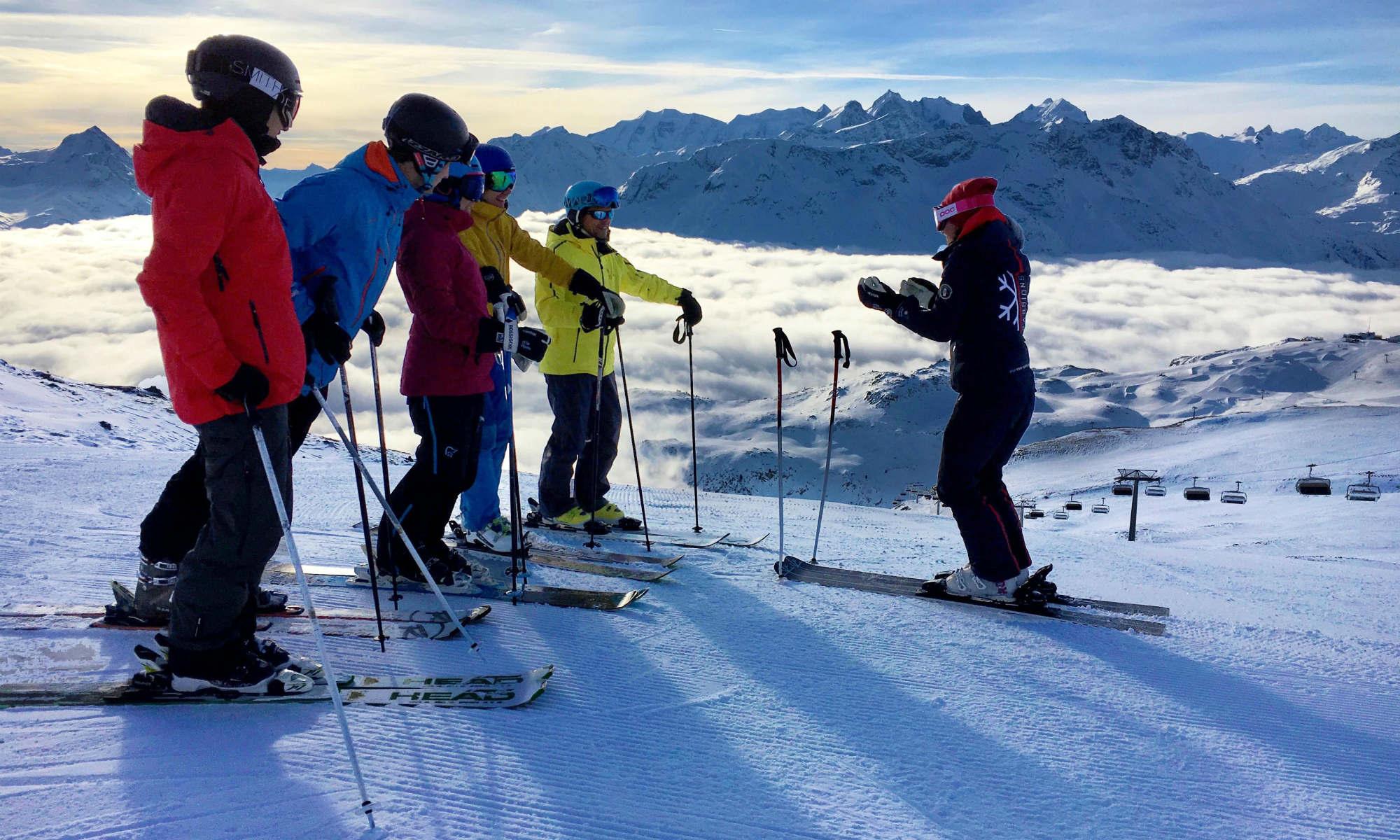 Eine Skilehrerin bringt Erwachsenene auf einer Skipiste in St. Moritz die Skitechnik bei.