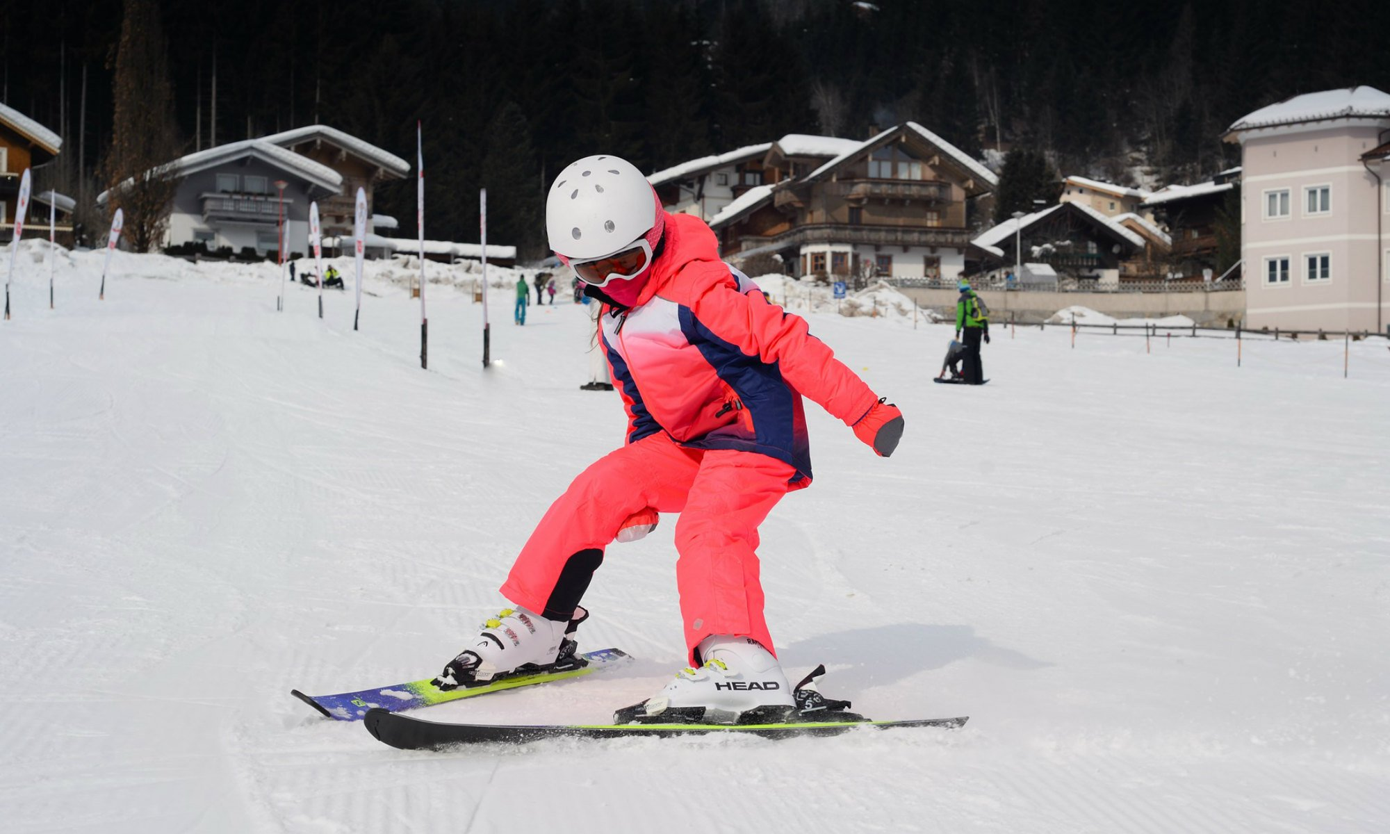 Child skiing down the slope in a snow plough turn.