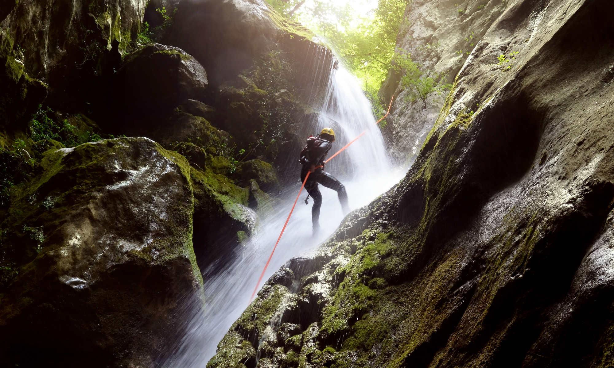 Ein Mann seilt sich beim Canyoning an einem Wasserfall in einer Schlucht ab.
