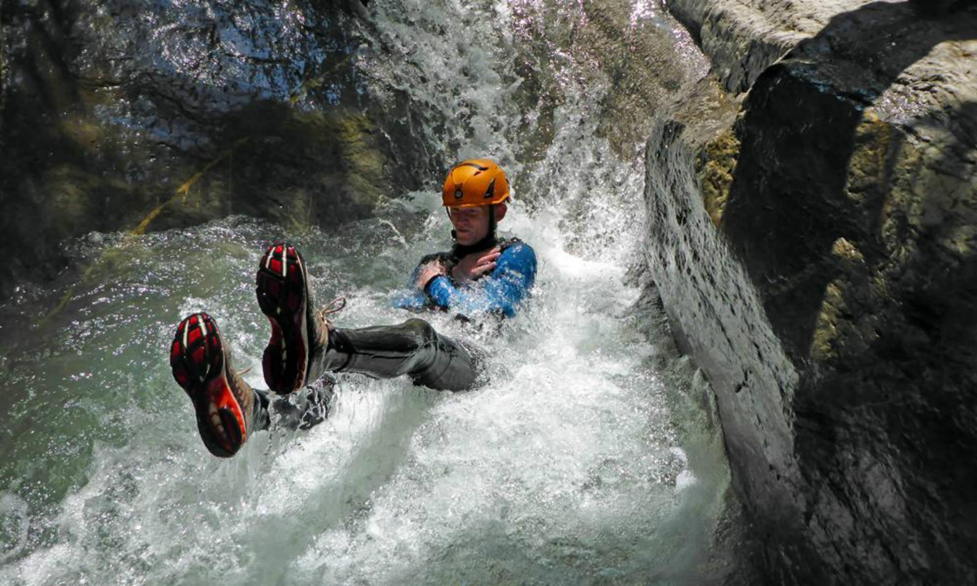 Ein Canyoning Teilnehmer rutscht eine Naturrutsche im Ostertaltobel im Allgäu hinunter.