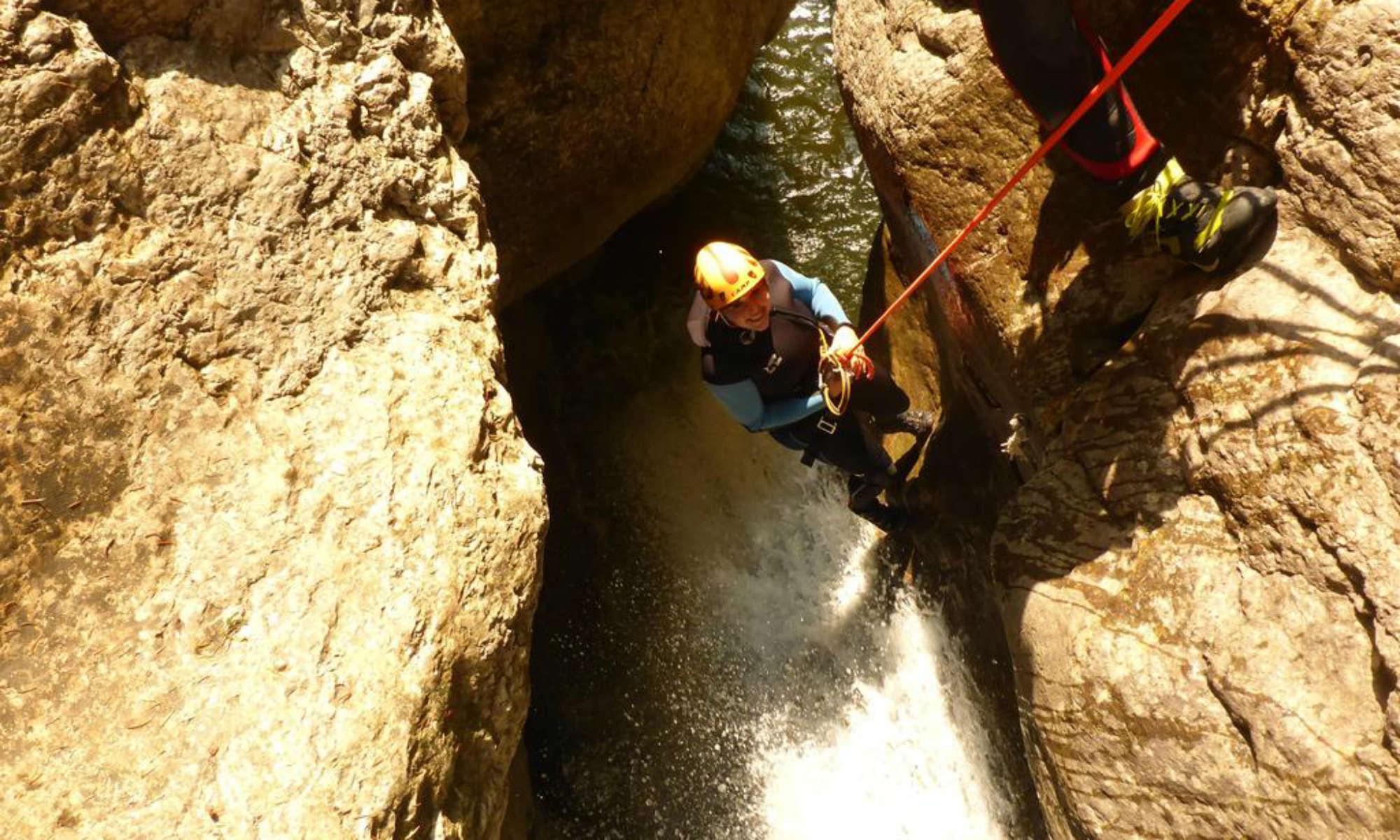 Eine Canyoning Teilnehmerin seilt sich beim Schwarzwasserbach im Allgäu an einem Felsen hinunter.