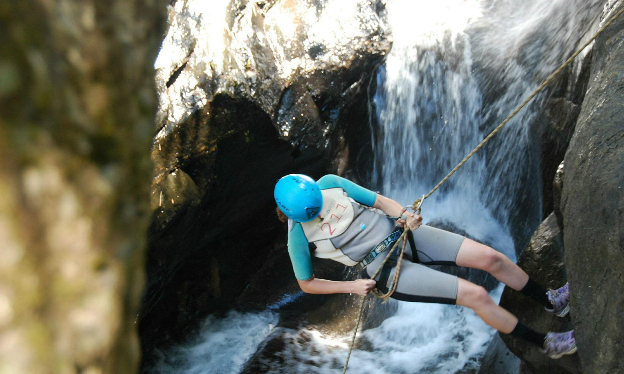 Ein Canyoning Teilnehmer seilt sich sicher eine 15 m hohe Felswand in der Starzlachklamm hinunter.