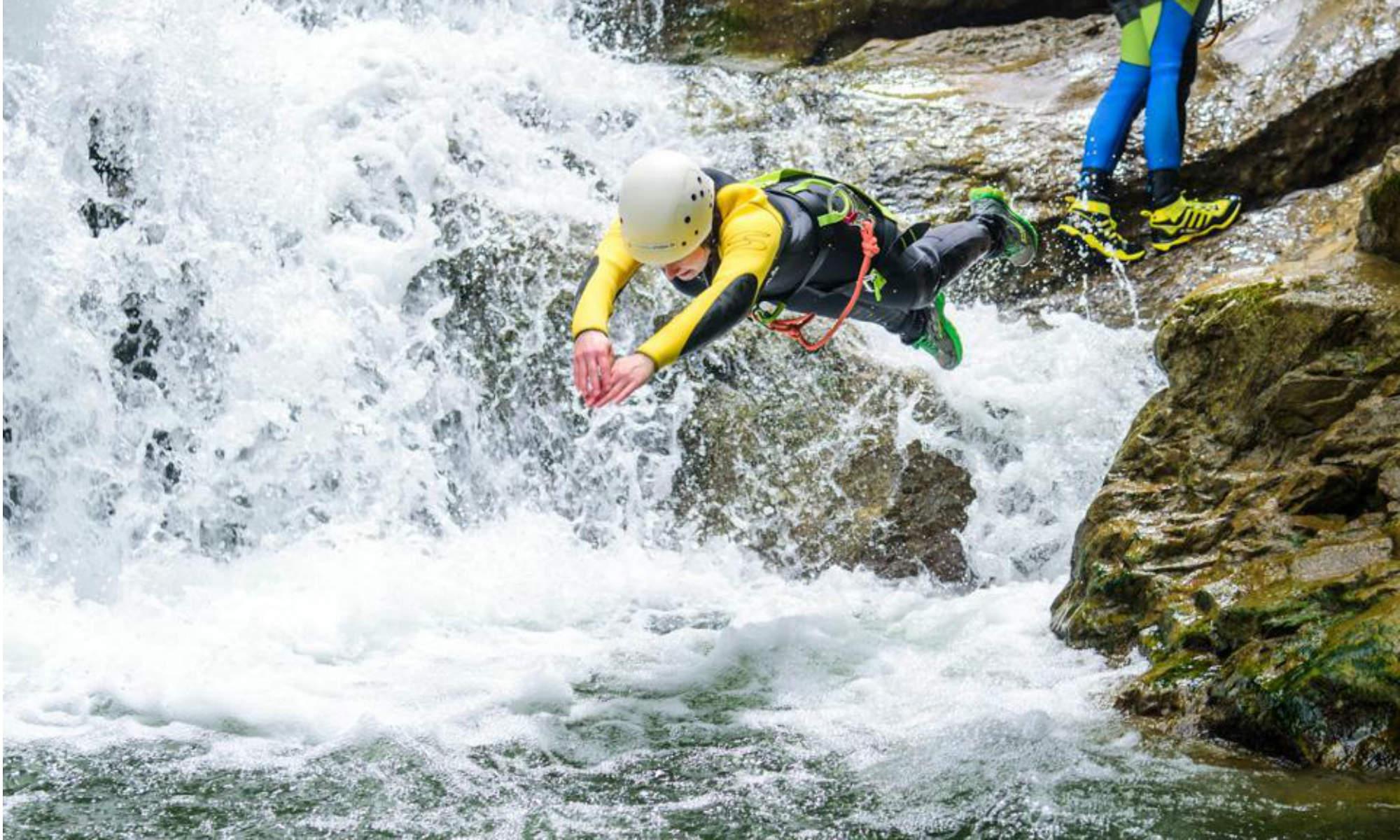 Ein Teilnehmer einer Canyoning Tour springt in ein Wasserbecken im Allgäu.