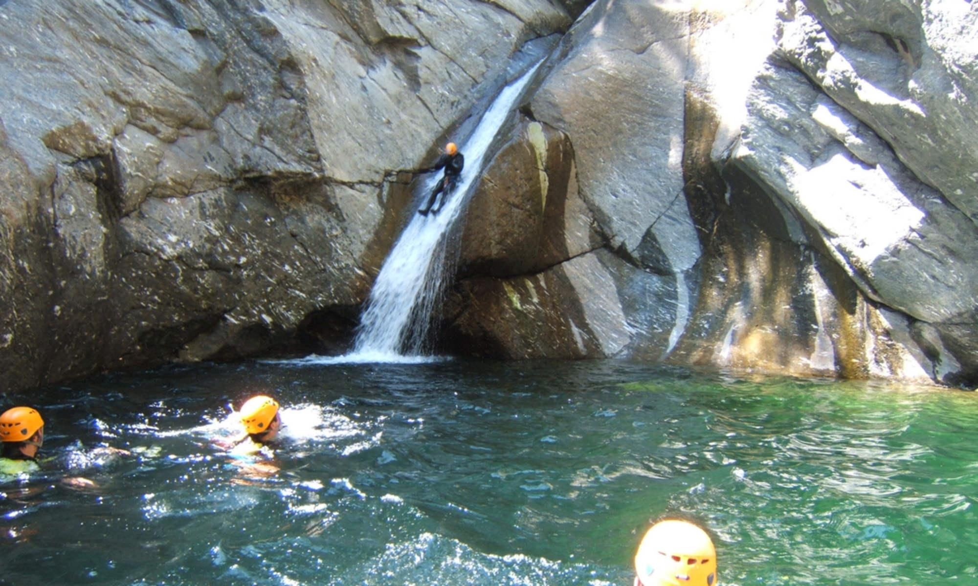 Teilnehmer ein Canyoning Tour auf einer natürlichen Wasserrutsche und in einem Wasserbecken in der Schlucht Chalamy in Italien.