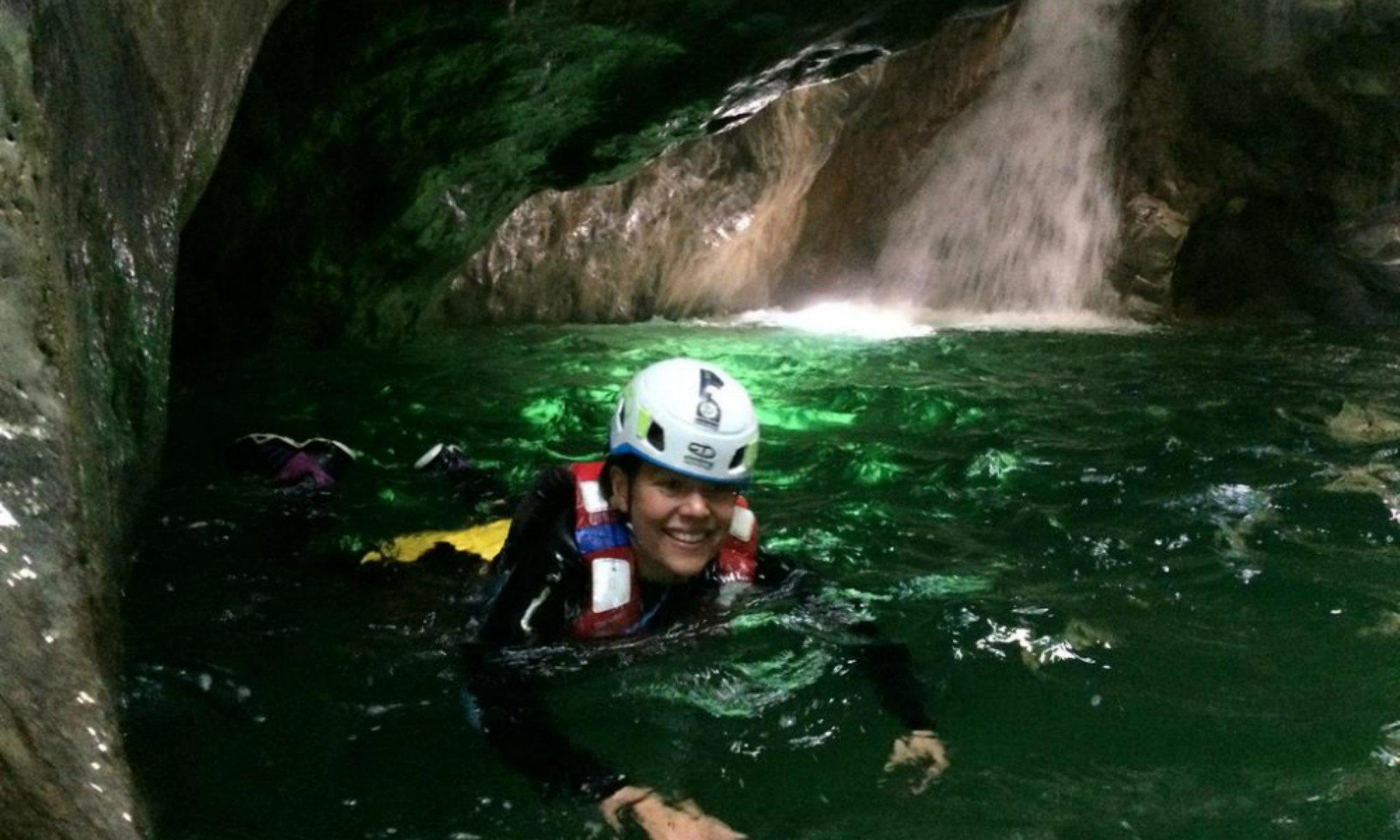 Una ragazza nuota nelle acque del Palvico durante un'escursione di canyoning al Lago di Garda.