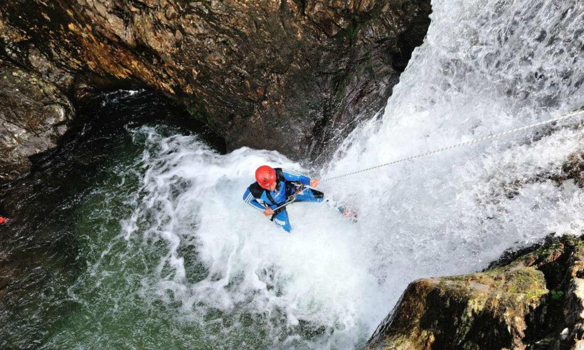Ein Mann seilt sich beim Canyoning in Österreich an einer Felswand der Auerklamm ab.