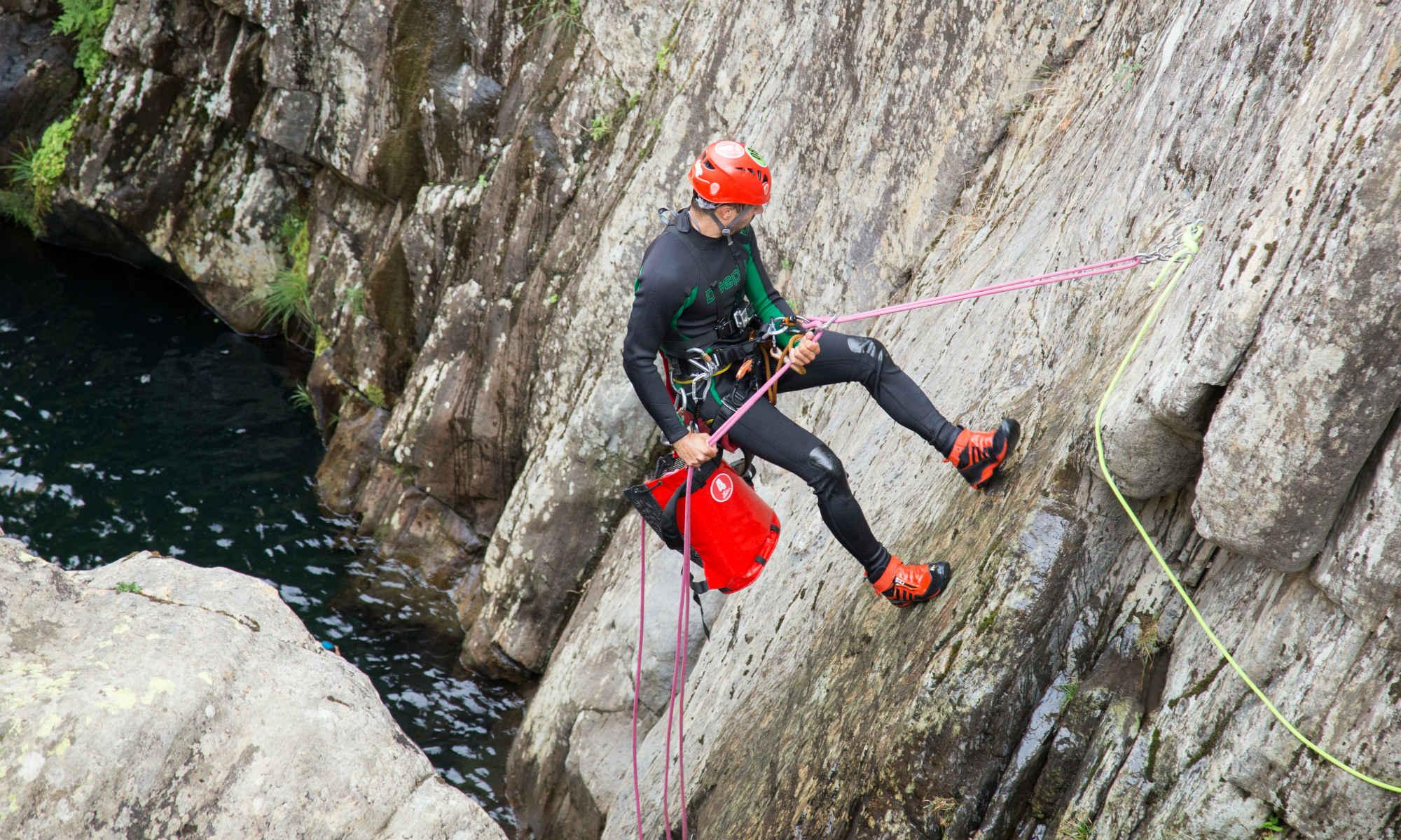 Ein Mann seilt sich mit Sicherung an einer Felswand ab.